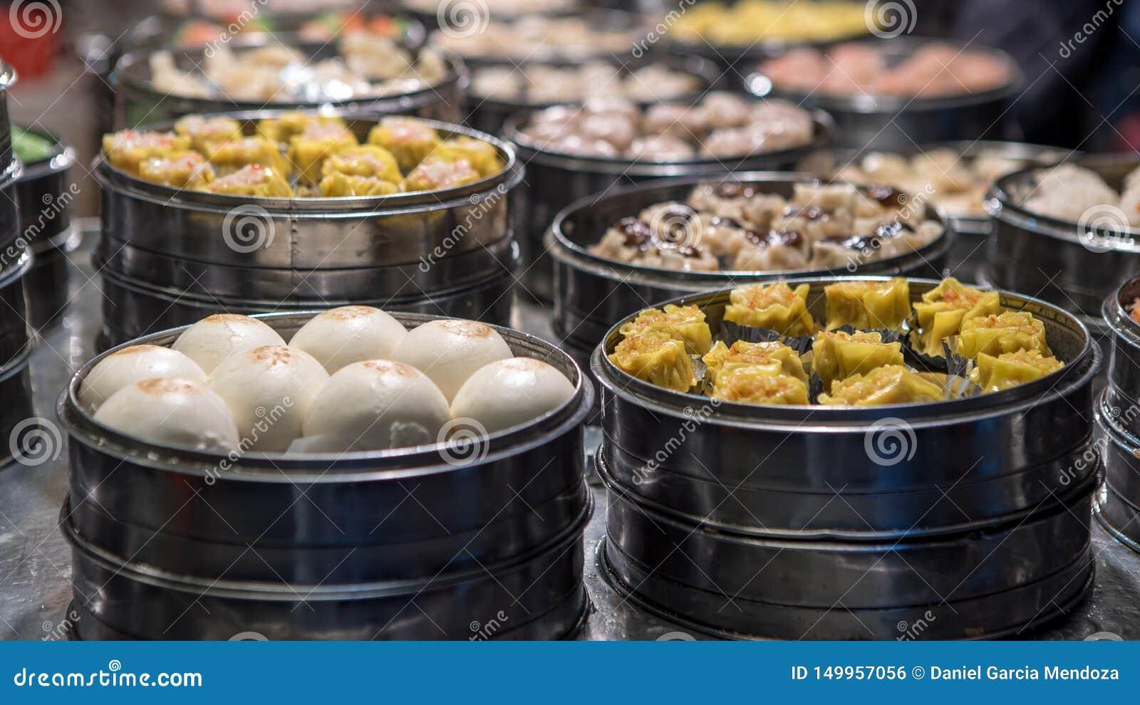 Vendedor que vende a bolinha de massa e o shaomai no mercado asiático do alimento da rua de Taiwan