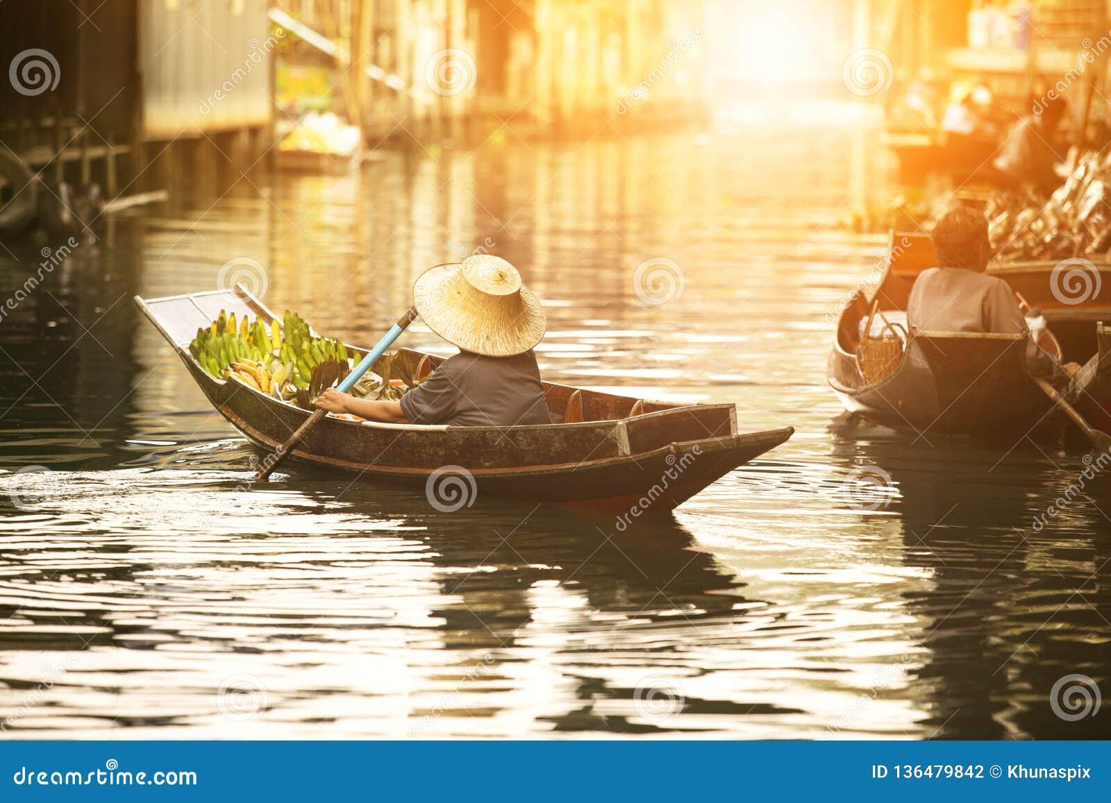 Vendedor tailandés de la fruta que navega el barco de madera en mercado flotante de la tradición de Tailandia