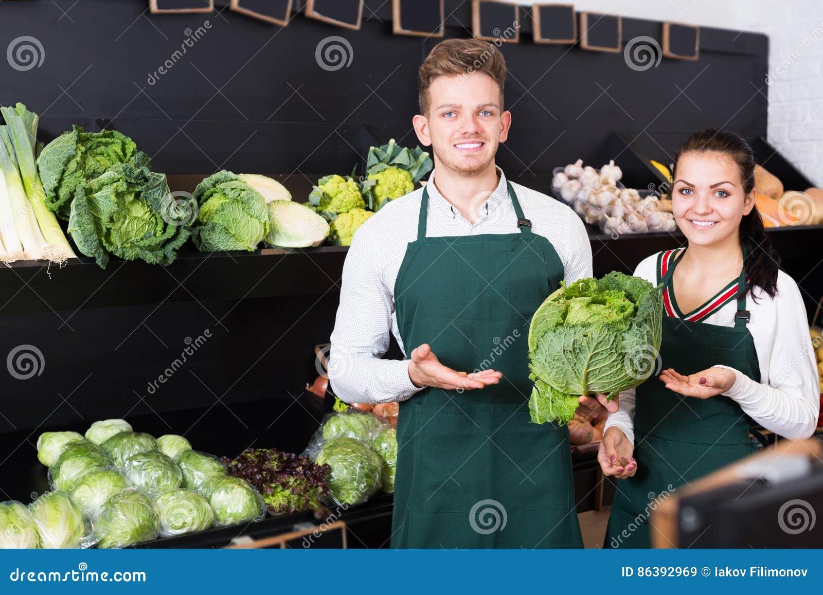 Vendedores del hombre joven y de la mujer que exhiben el surtido