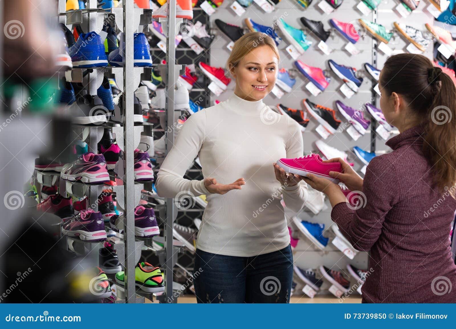 052e398aa603ac Jeune vendeur féminin gai montrant un assortiment de chaussures dans le  magasin