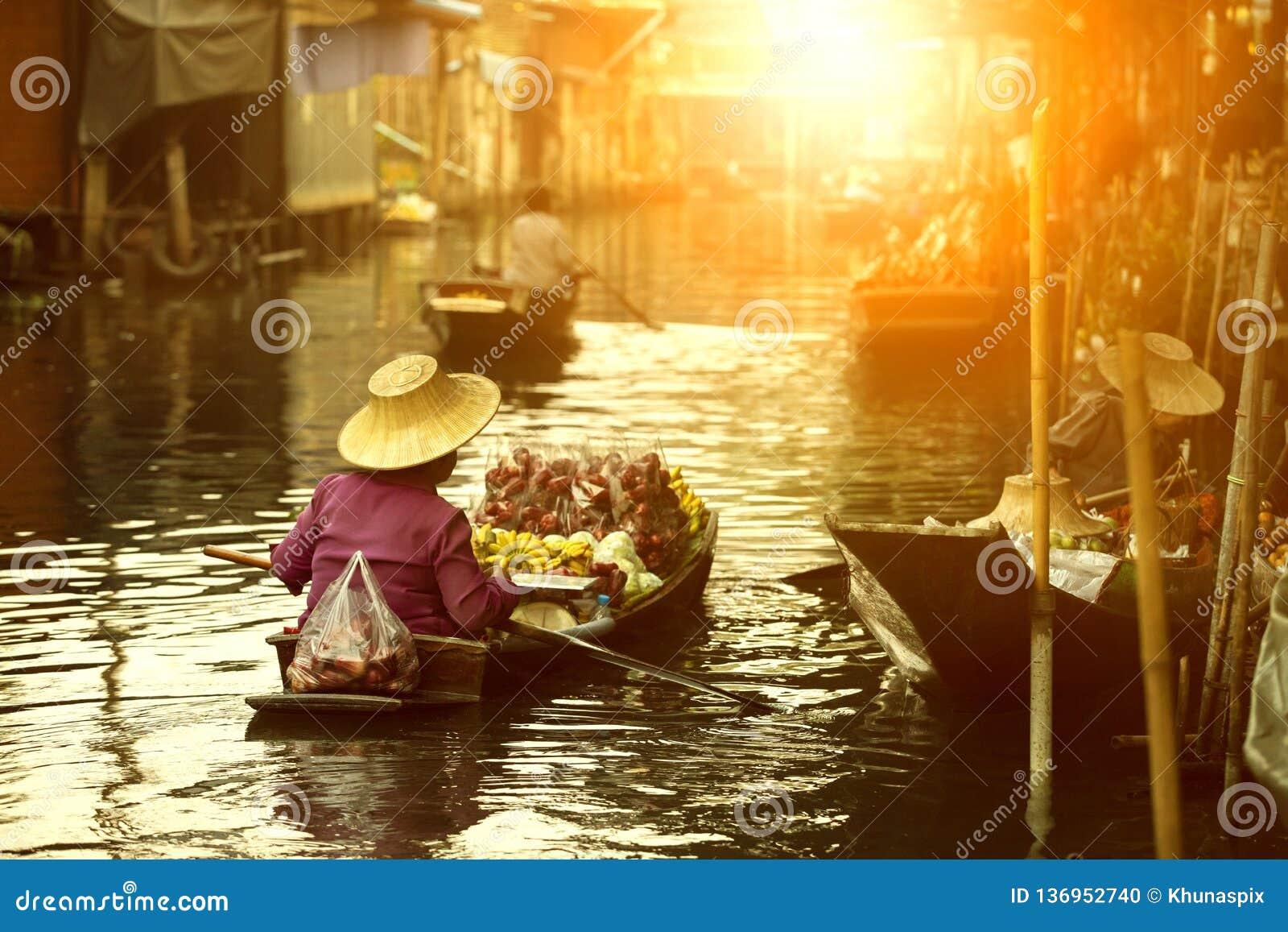 Vendeur thaïlandais de fruit naviguant le bateau en bois sur le marché de flottement de tradition de la Thaïlande