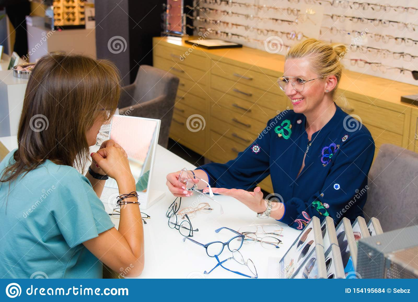 Vendeuse de salon d opticien avec son client choisissant des lunettes