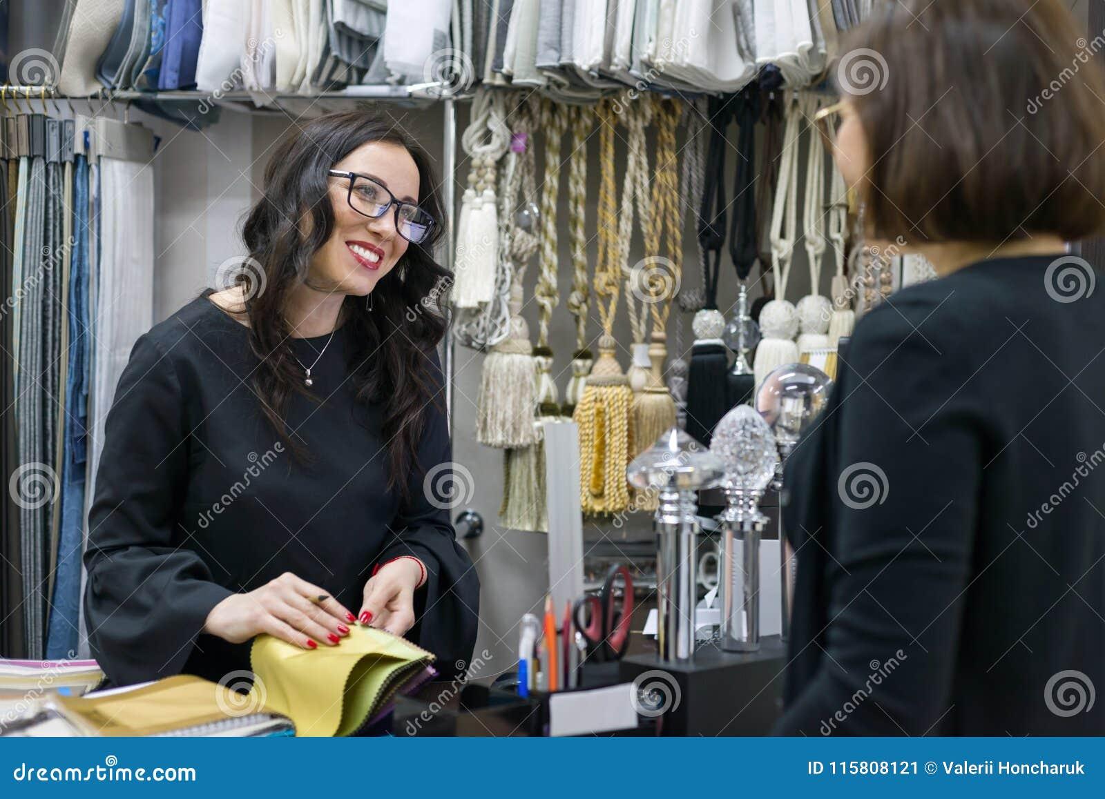 Venditore della donna nel deposito interno del tessuto con il cliente