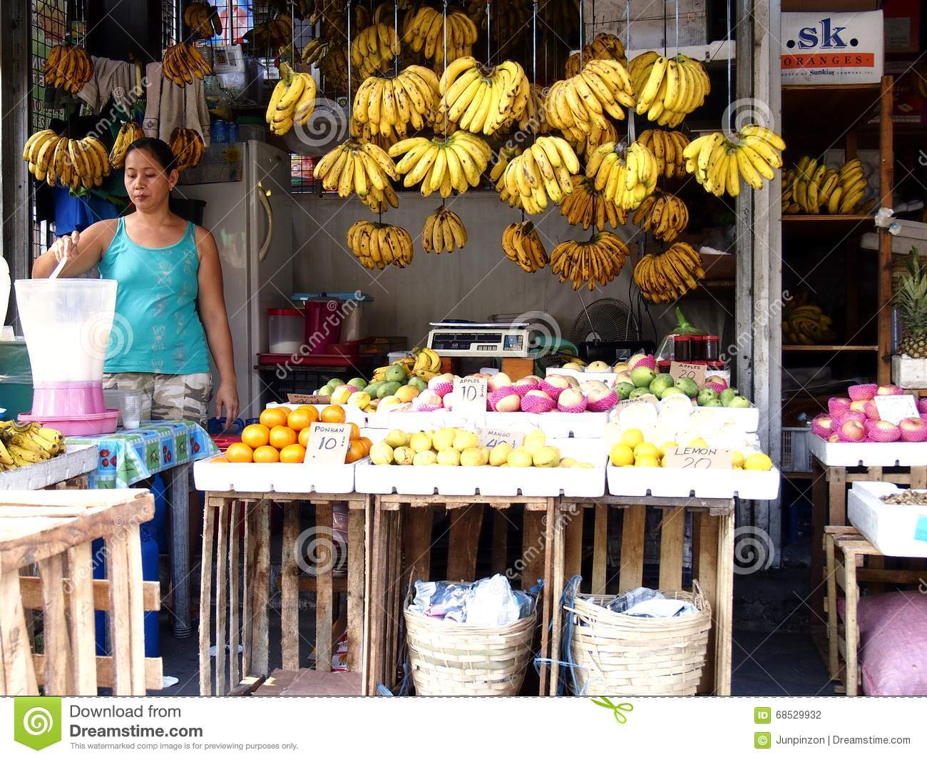 A vendor prepares fruit juice in her fruit stand in a market in Cainta, Philippines