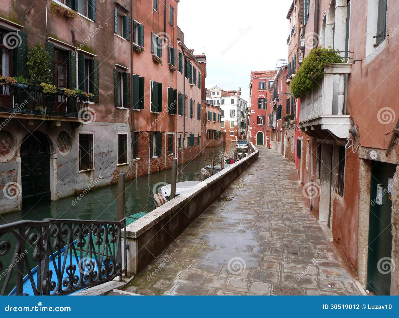 Venedig - en sikt av en liten kanal med fartyg och gatan