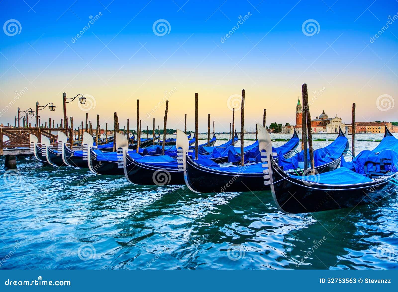 Venedig, gondoler eller gondole på solnedgång och kyrka på bakgrund. Italien