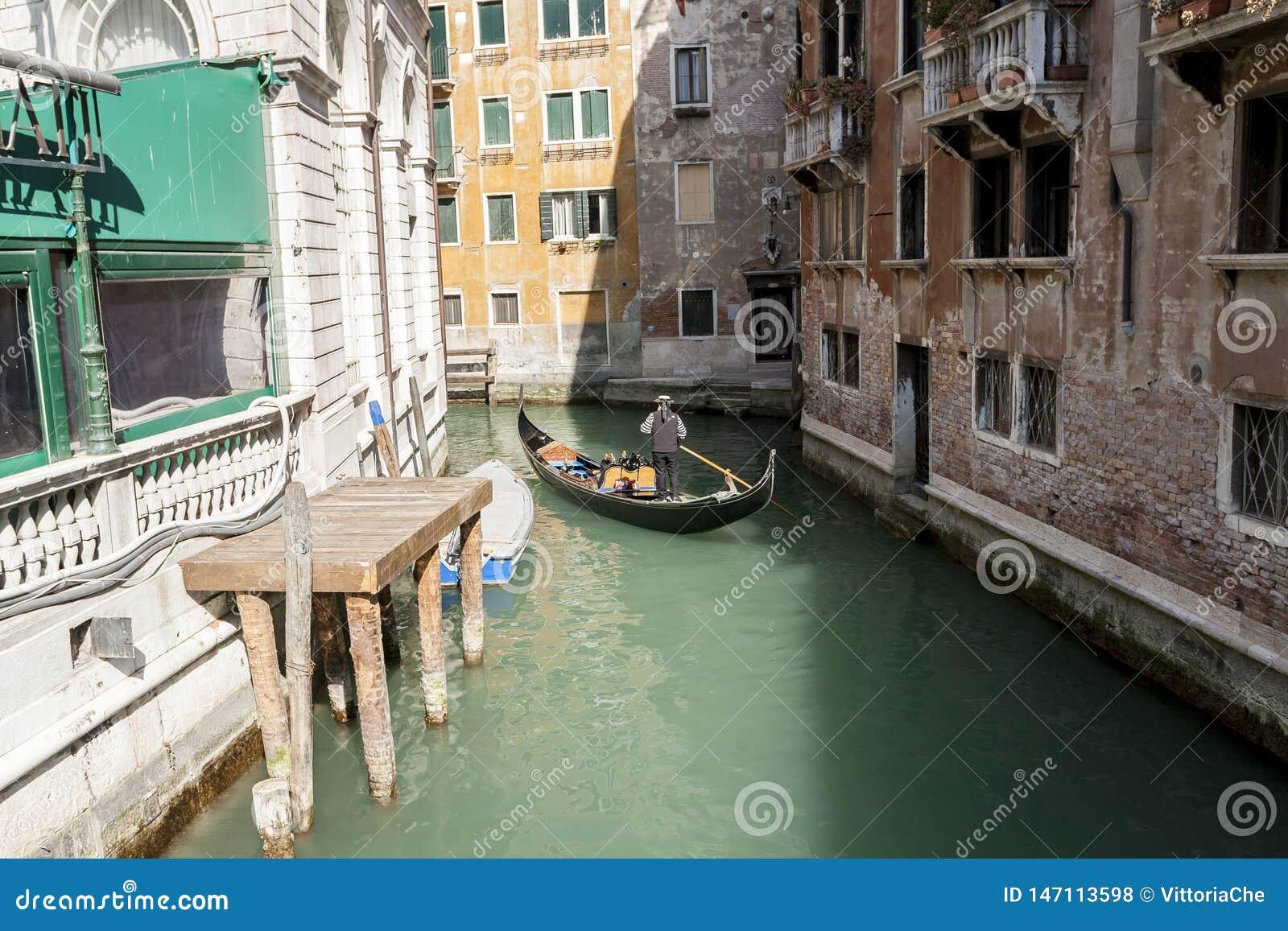 Venedig, Italien - 11. M?rz 2012: Typische Gondel mit Gondoliererudersport entlang einem schmalen Kanal in Venedig