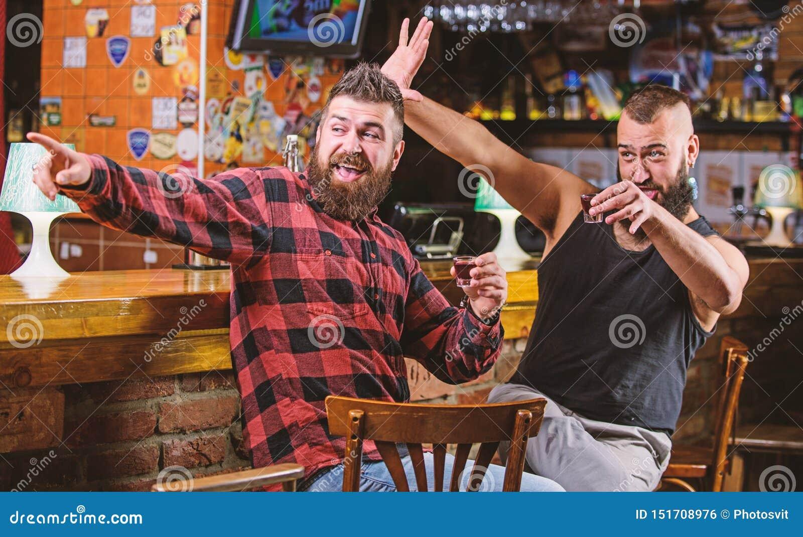 Venerd? si rilassa in pub Incoraggia il concetto Alcool bevente dell uomo barbuto brutale dei pantaloni a vita bassa con l amico