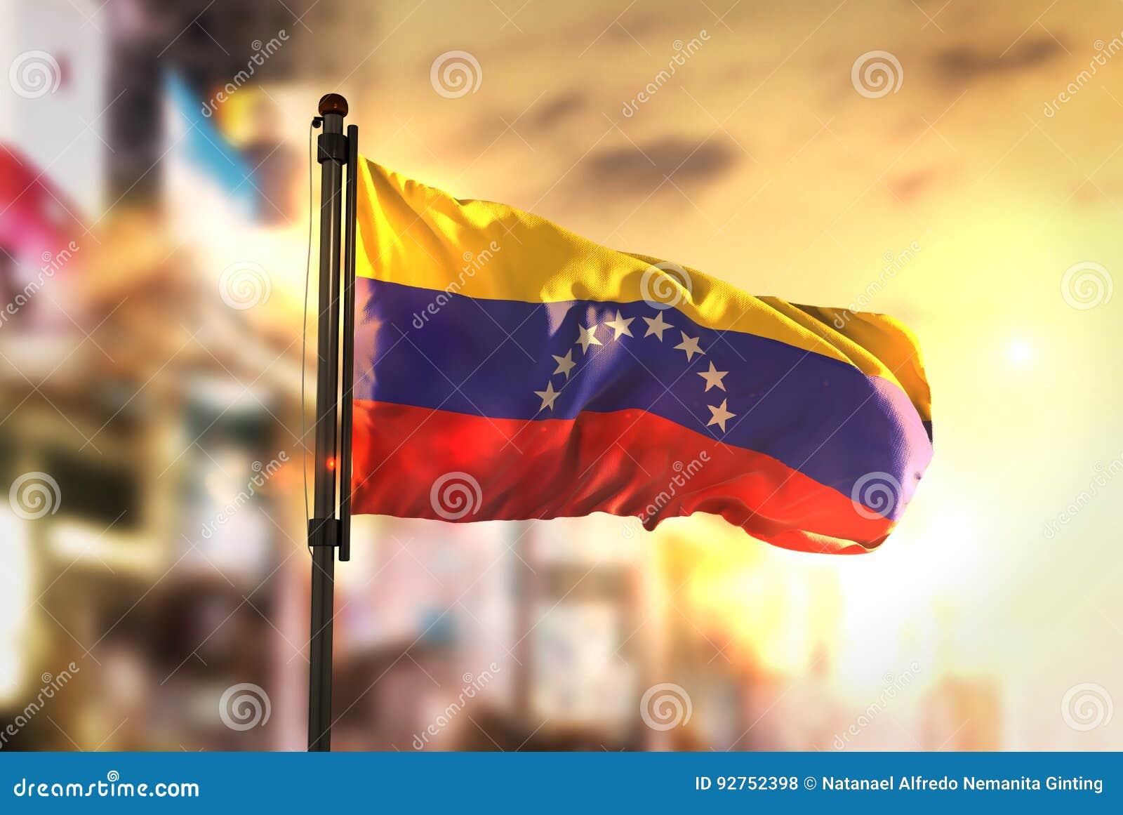 Venezuela flagga mot suddig bakgrund för stad på soluppgång Backli