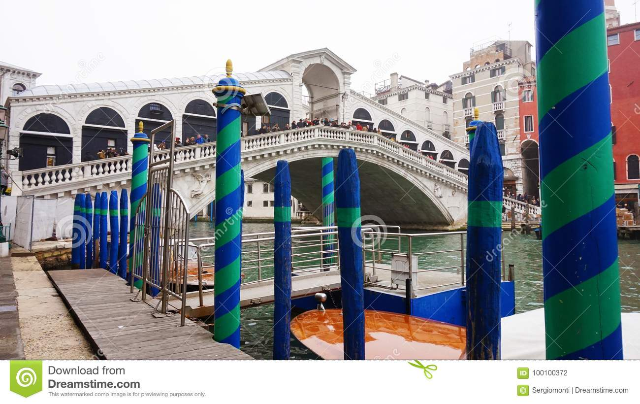 VENICE, ITALY - FEBRUARY 23, 2017: Panoramic view of Canal Grande with pole to mooring green and blue and the Rialto Bridge on the