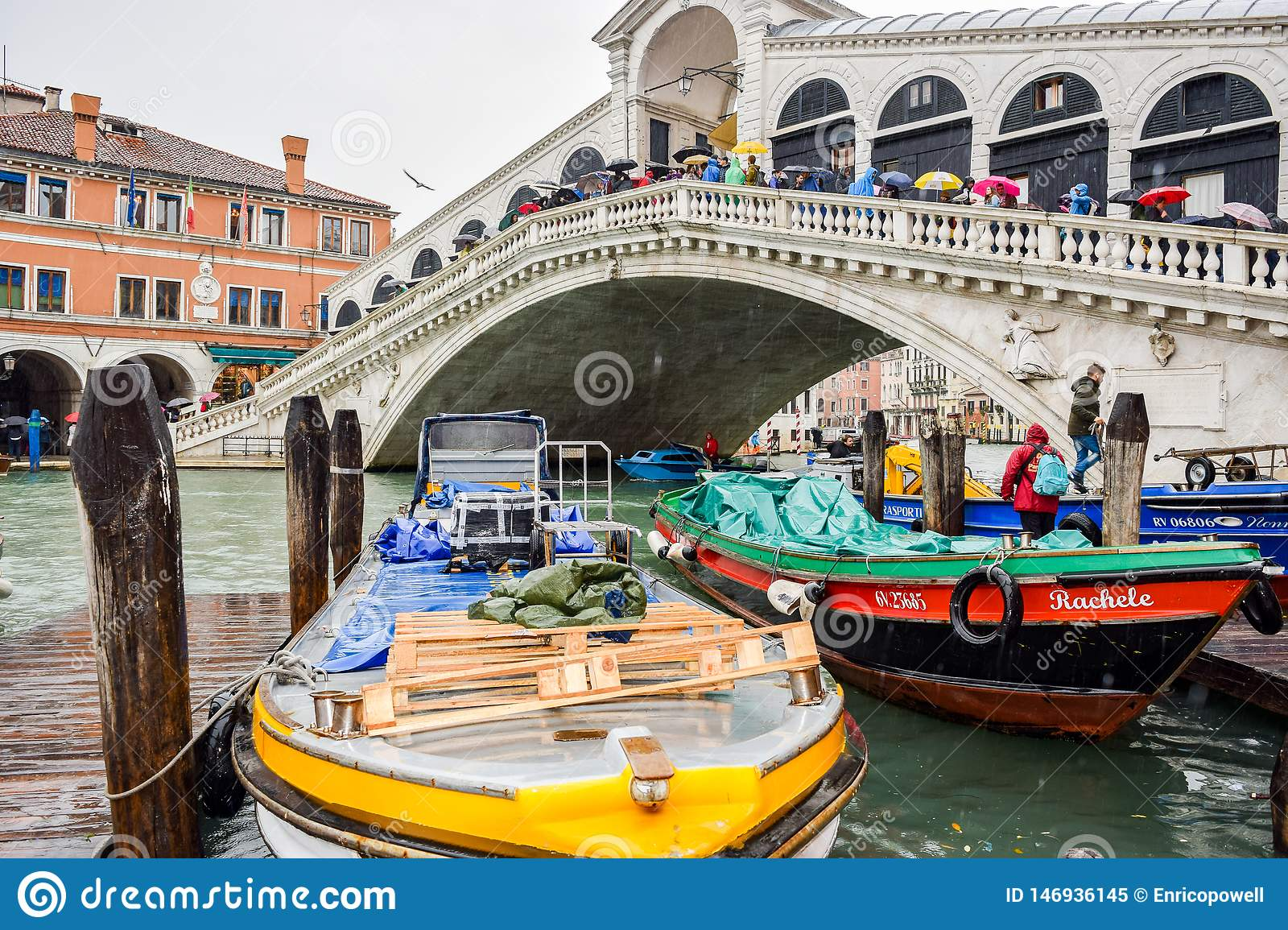 Tourists on a rainy day at Rialto Bridge on the Grand Canal in Venice, Italy.