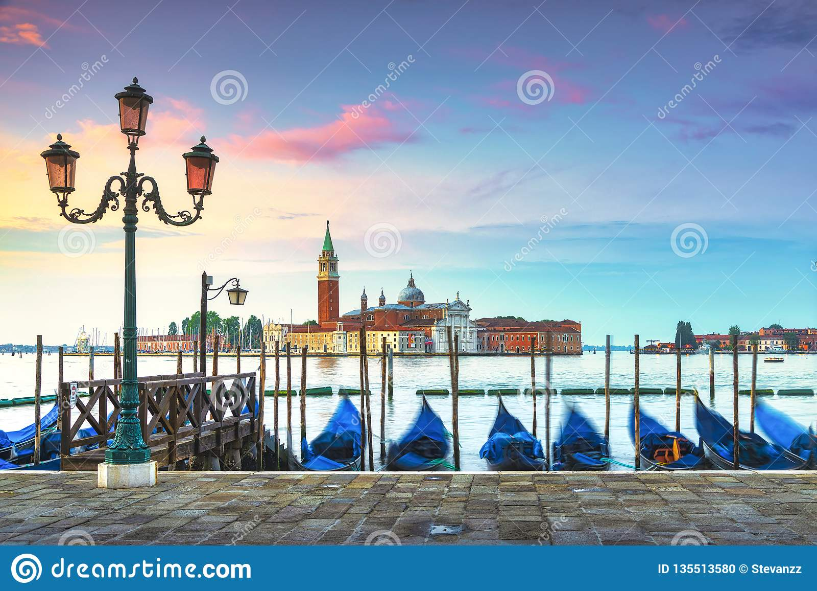 Venice lagoon, San Giorgio church, gondolas and poles. Italy