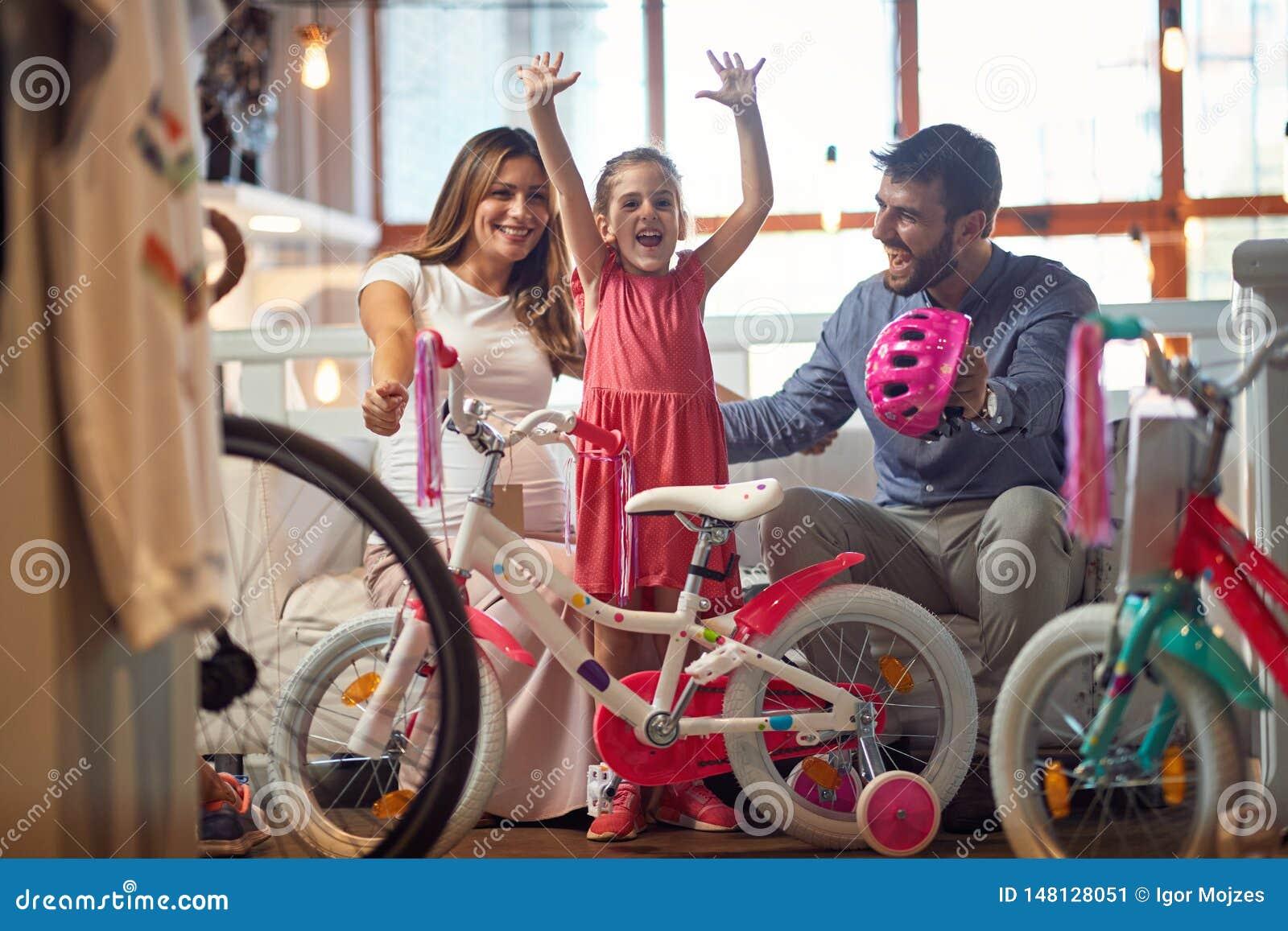Venta, consumerismo y concepto de la gente - familia feliz con el niño y la nueva bicicleta que hace compras