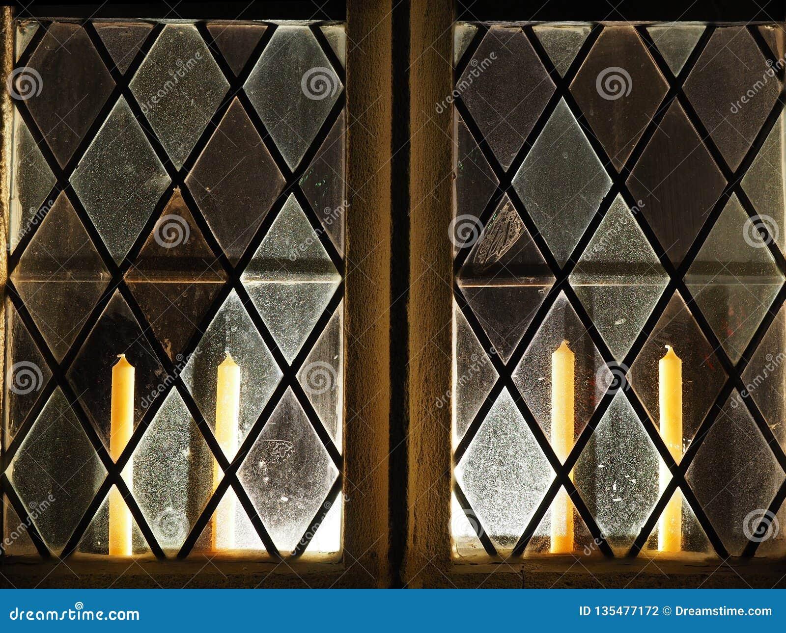Ventana retroiluminada de la iglesia con las velas dentro
