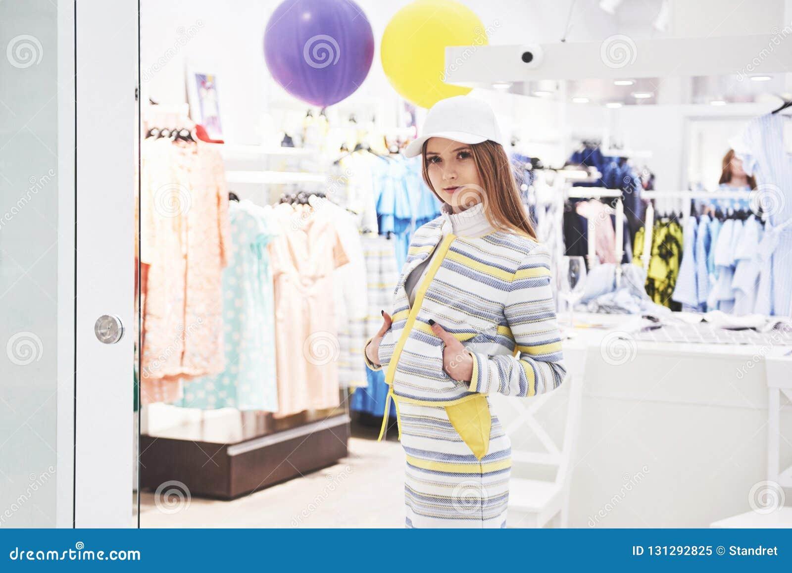Vente, mode, consommationisme et concept de personnes - jeune femme heureuse avec des sacs à provisions choisissant des vêtements