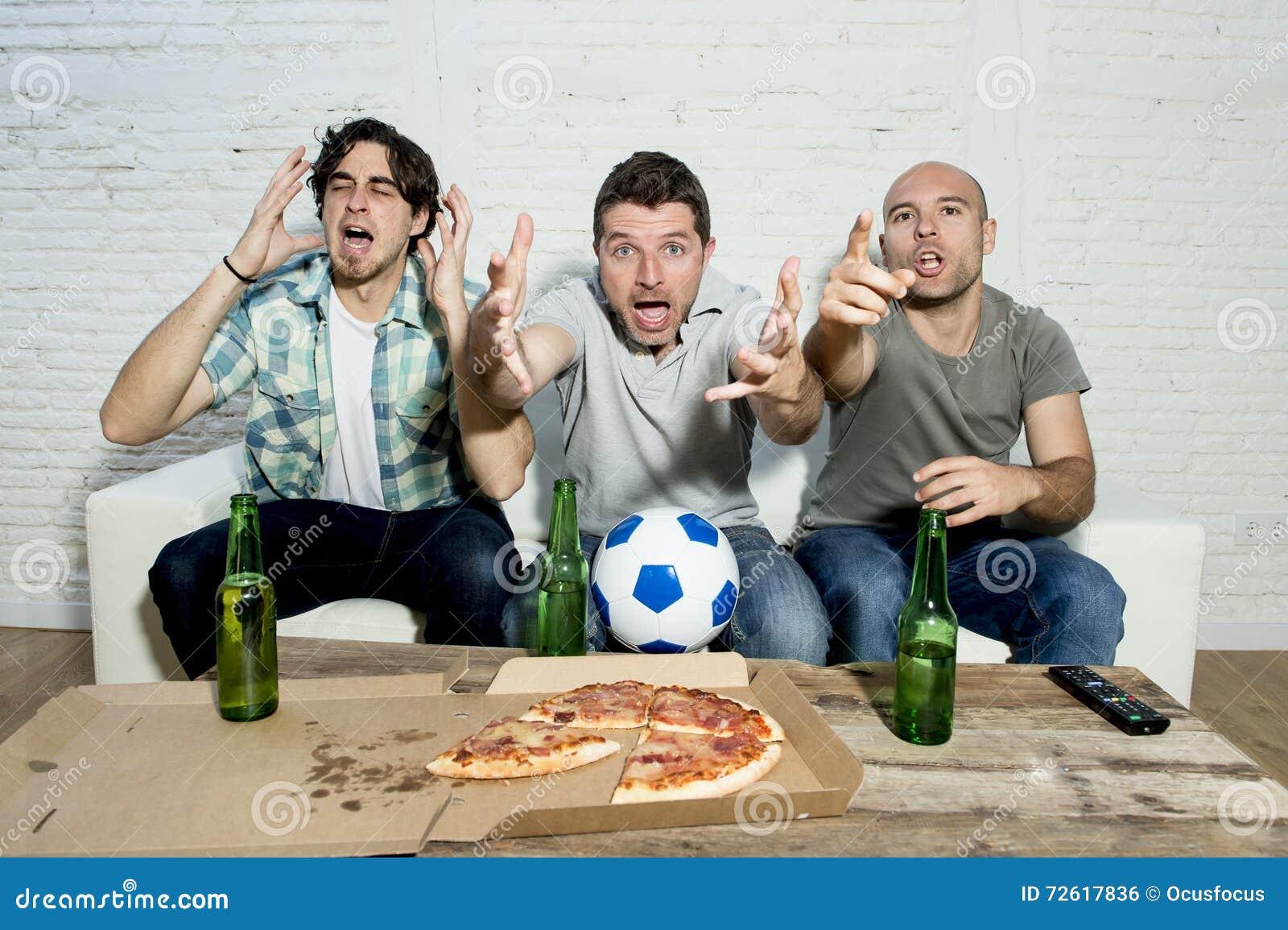 Ventilators die van de vrienden de fanatieke voetbal TV-op gelijke met bierflessen en pizza letten die aan spanning lijden