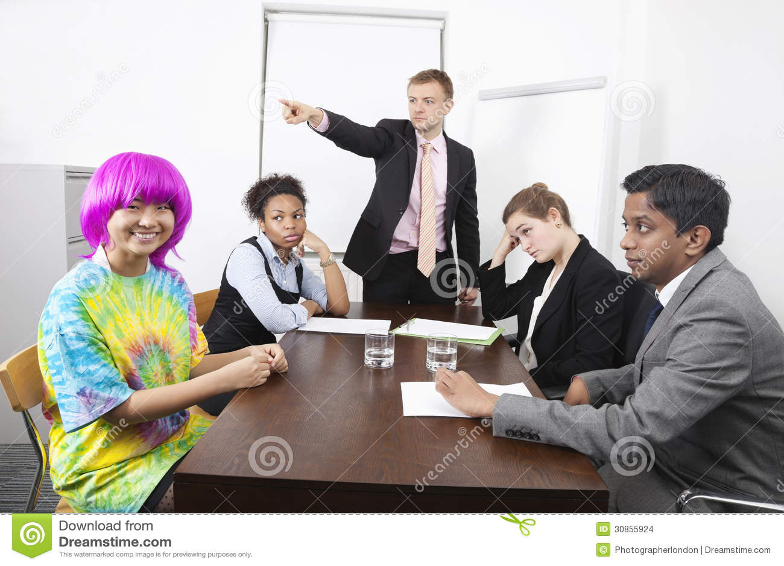 Verärgerte multiethnische Wirtschaftler mit Kollegen in der rosa Perücke bei der Sitzung