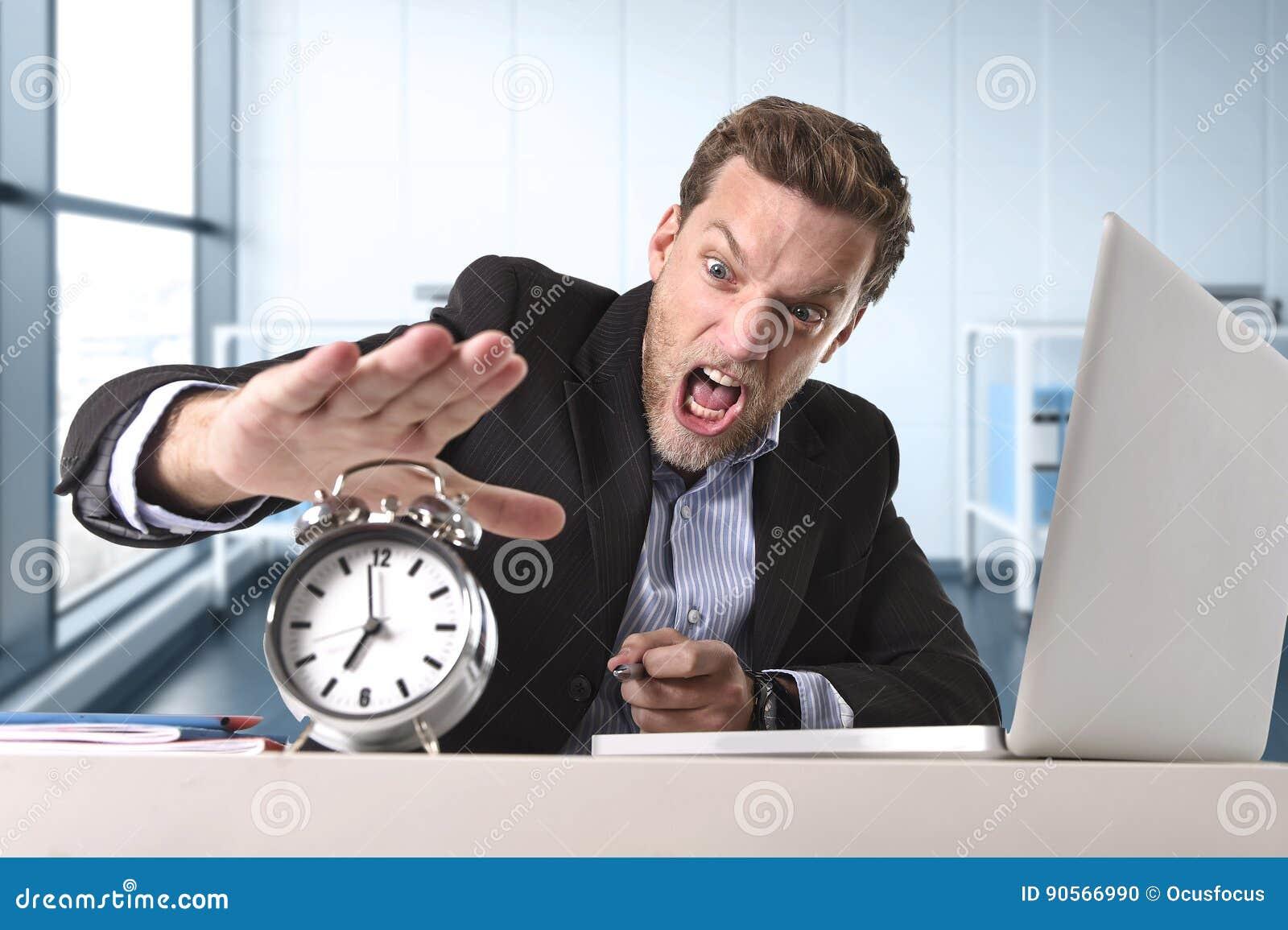 Verärgerter ausgenutzter Geschäftsmann am Schreibtisch betont und frustriert mit Computerlaptop und -Wecker