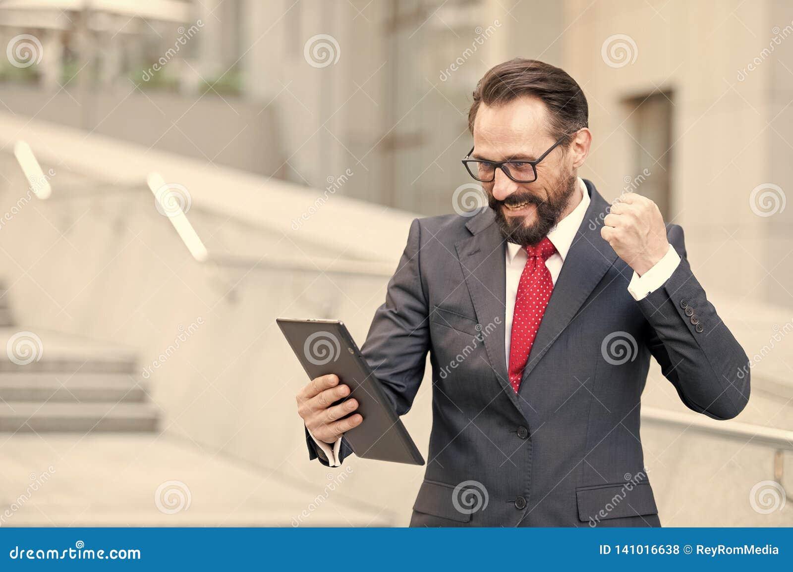 Verärgerter bärtiger Geschäftsmann kleidete in der blauen Klage an, die mit der Faust tablet während Büros der Videokonferenz des