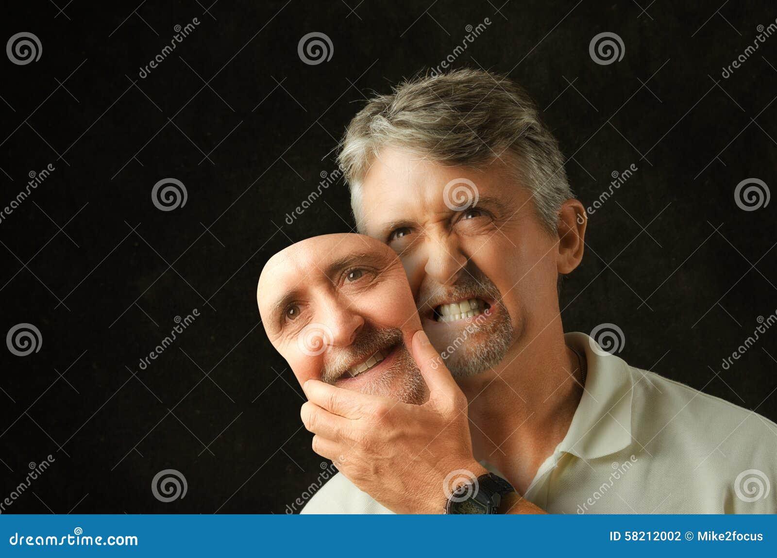 Verärgerter emotionaler Mann der bipolaren Störung mit gefälschter Lächelnmaske