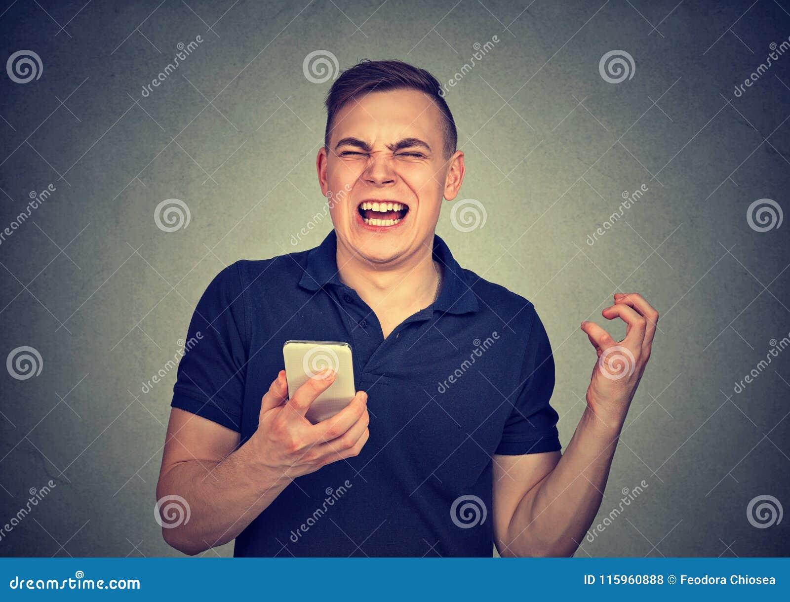 Verärgerter Mann, der an seinem Handy, erzürnt mit der geringen Qualität des schlechten Services von Smartphone schreit