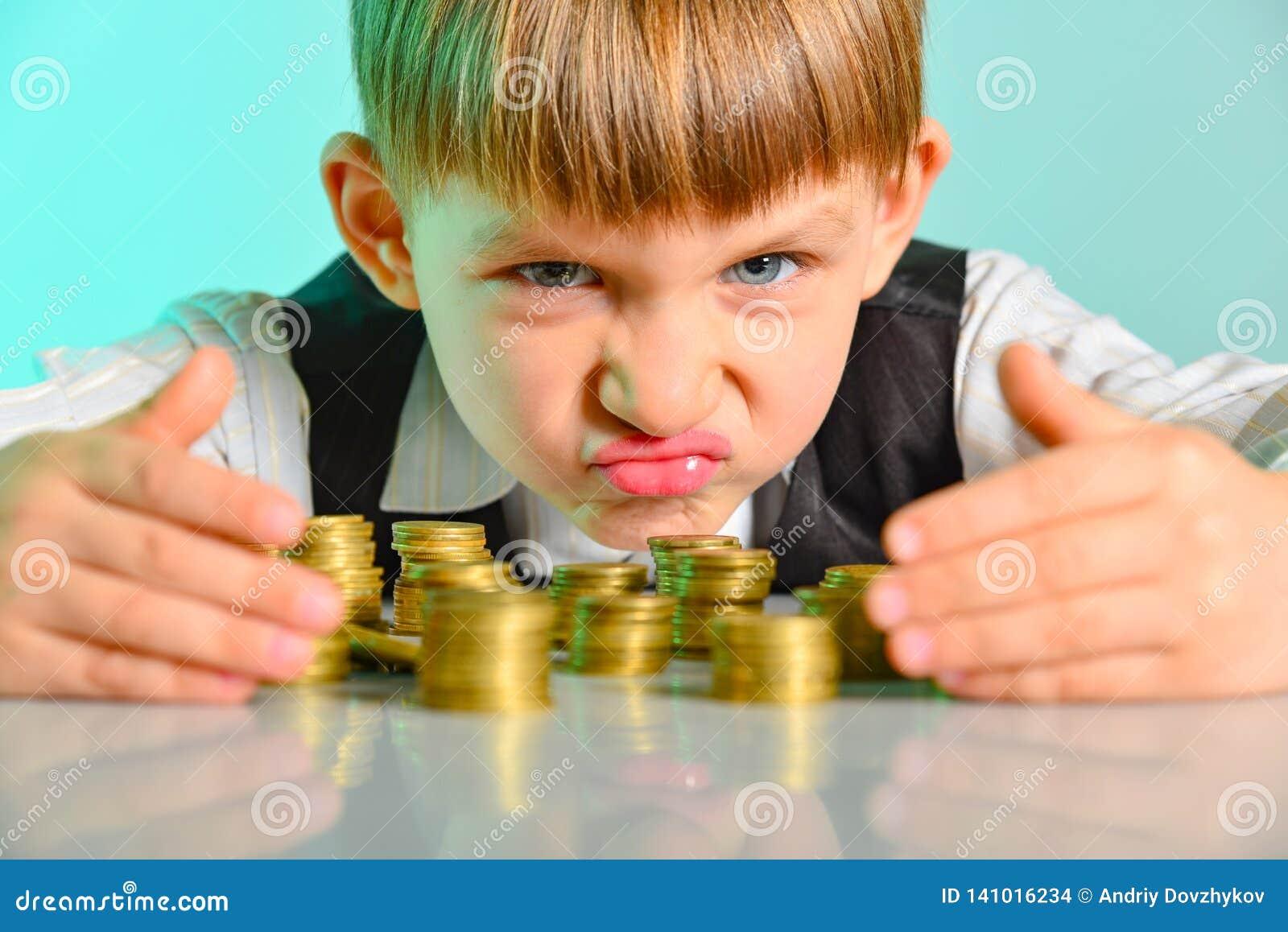 Verärgertes und gieriges Kind hält ihre Geldmünzen Das Konzept der Habsucht, der Habsucht und des Lasters von der Kindheit