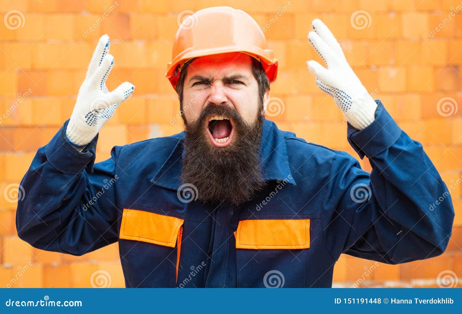 Ver?rgerter Erbauer Vorfall an einer Baustelle Sicherheitsregeln für Erbauer Bärtiger Mann im Sturzhelm auf dem Bau von
