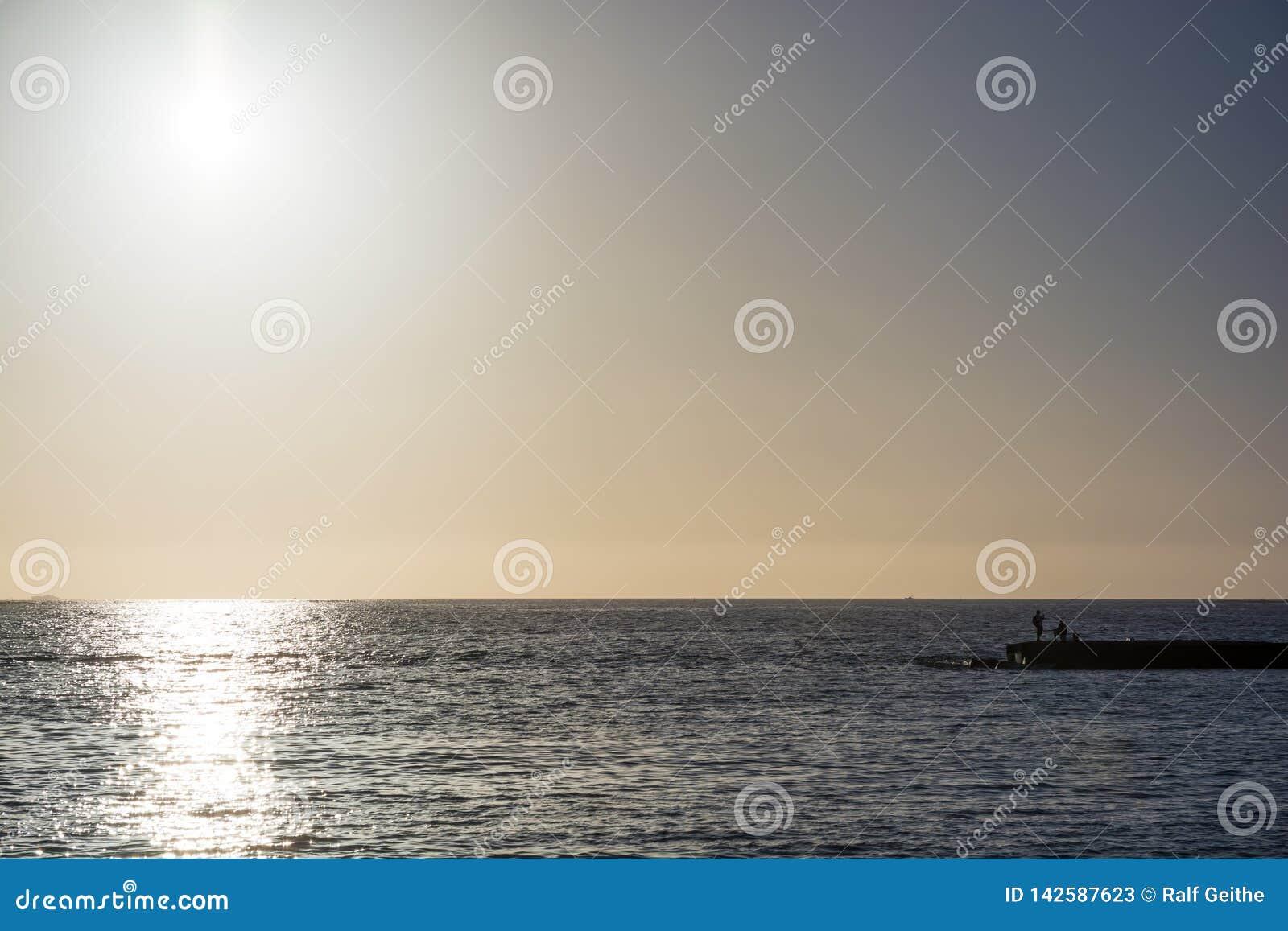 Ver van van een oceaan bij zonsondergang met vissers in de voorgrond