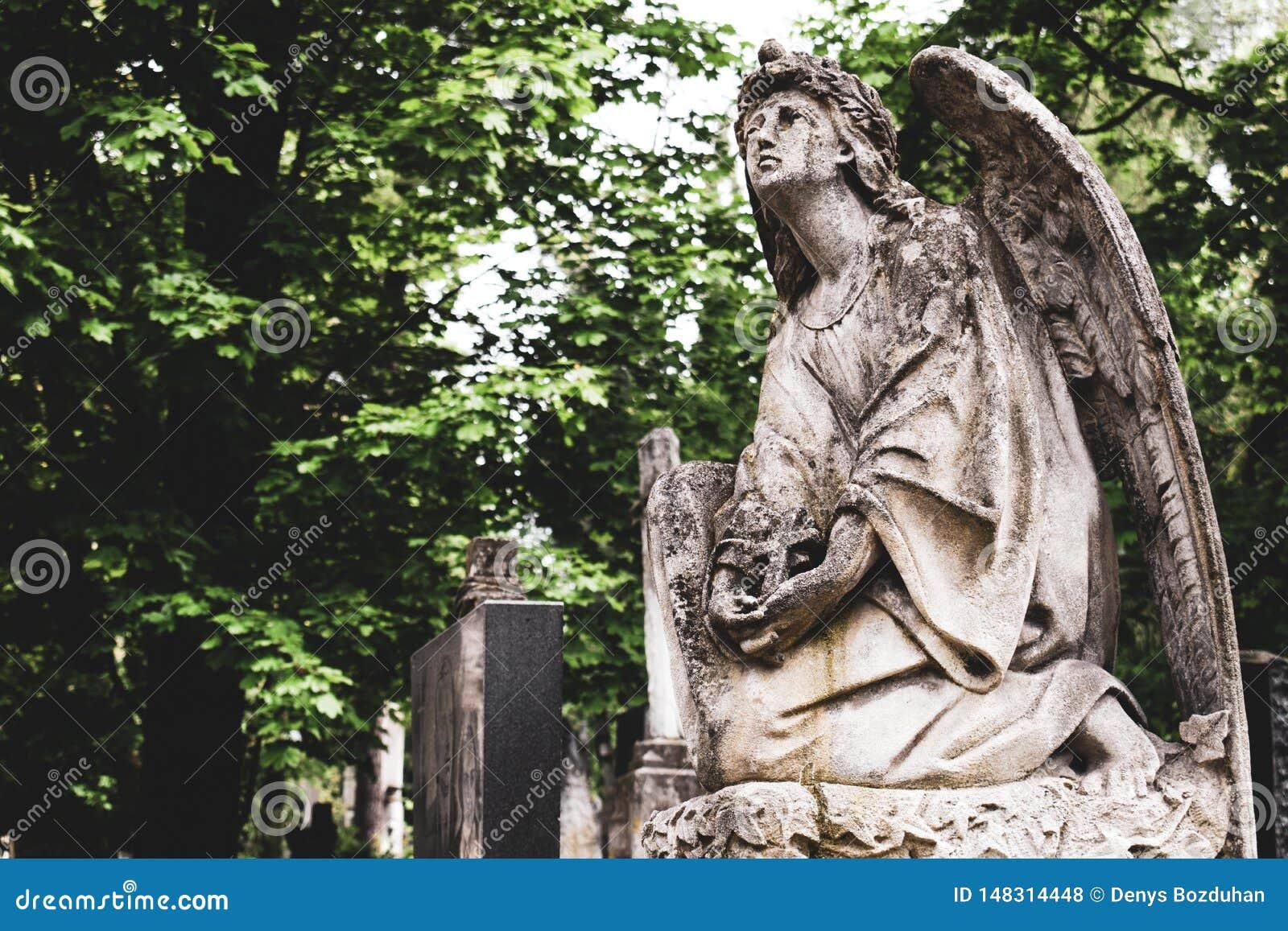 Veraltete alte Statur des Engels mit Kreuz auf Beerdigung auf Kirchhof in Lychakiv-Kirchhof, Lemberg