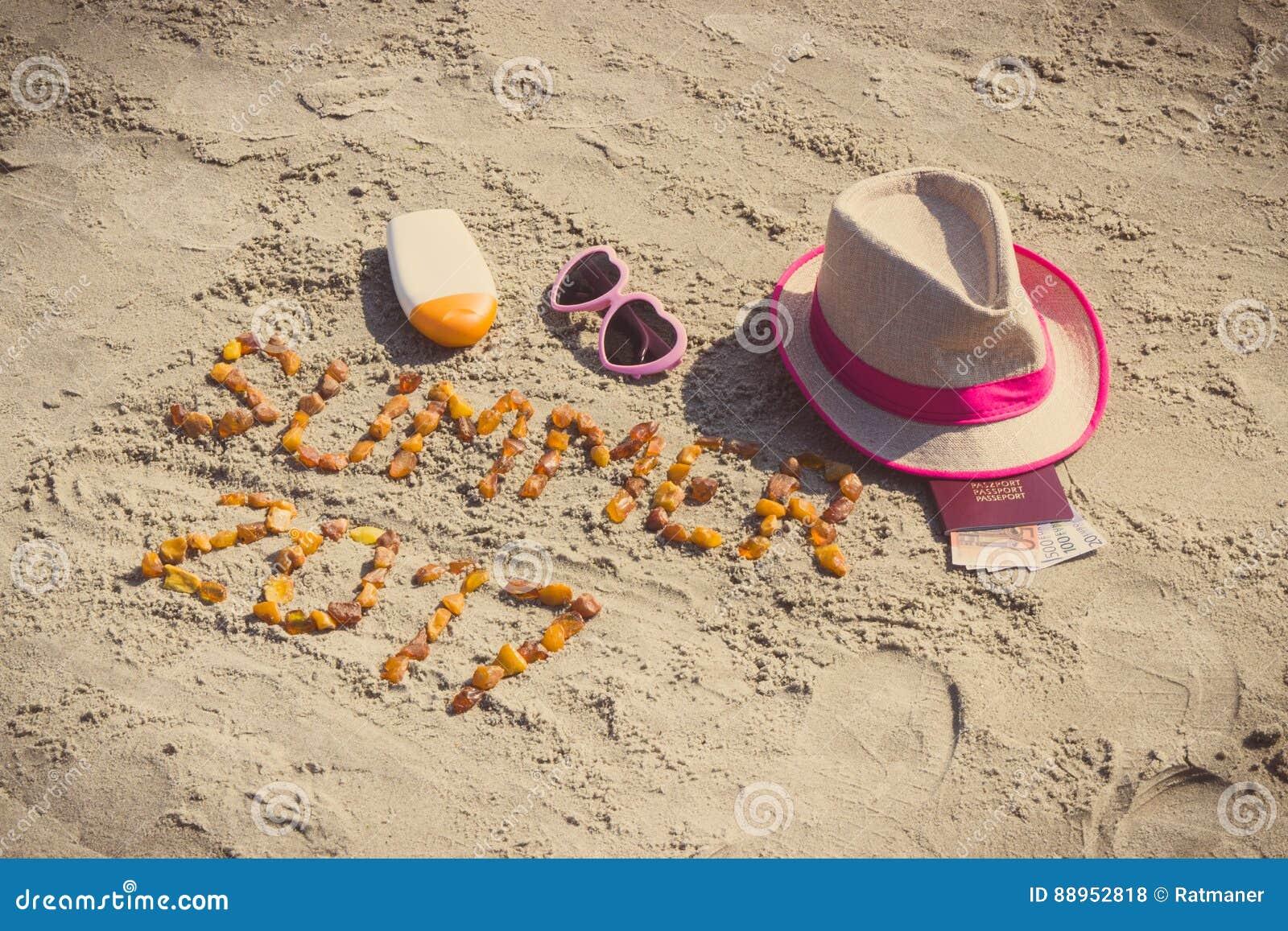 Verano 2017 de la inscripción, accesorios para tomar el sol y pasaporte con las monedas euro en la arena en la playa, tiempo de v