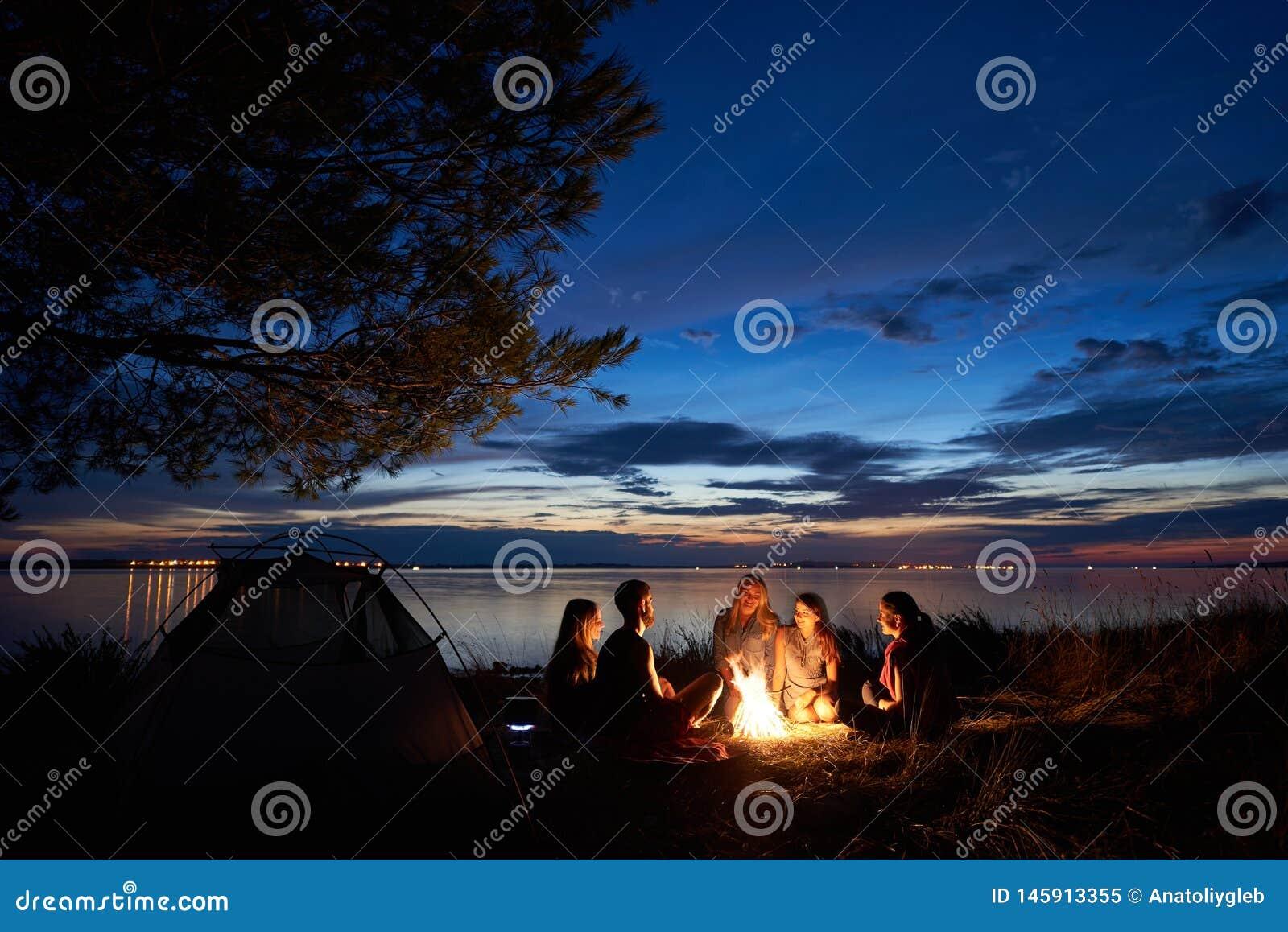 Verano de la noche que acampa en orilla Grupo de turistas jovenes alrededor de la hoguera cerca de la tienda debajo del cielo de