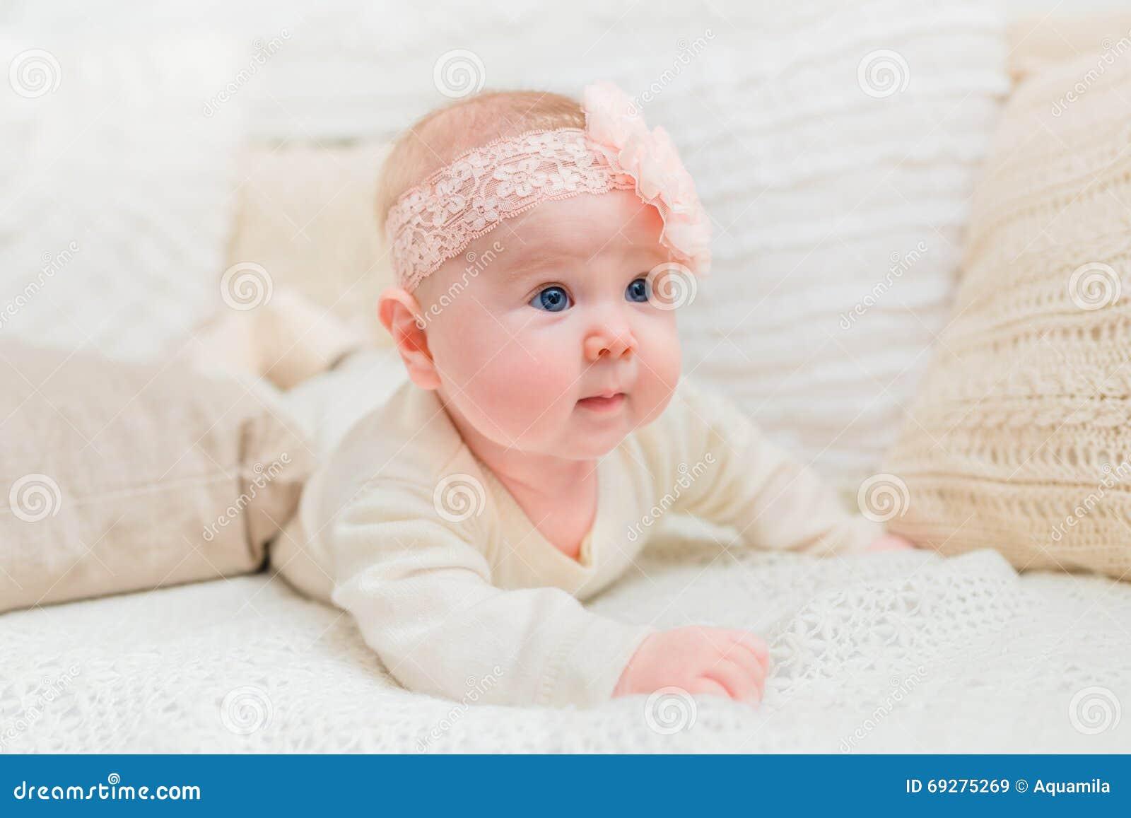 Verbaasd leuk weinig baby met mollige wangen die witte kleren en roze band die met bloem dragen op bed met gebreide hoofdkussens