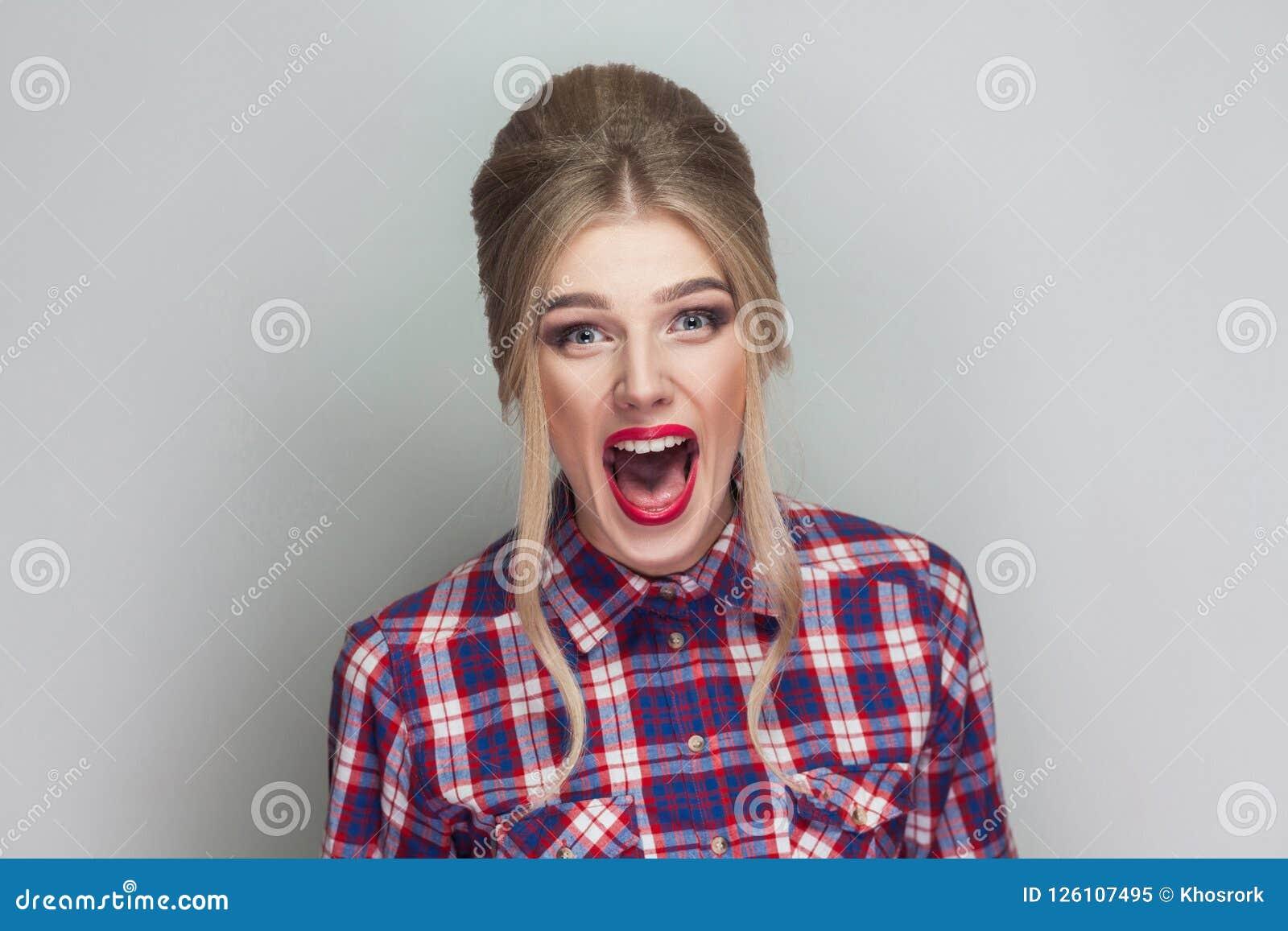 Verbaasd mooi blondemeisje met roze geruit overhemd, collecte