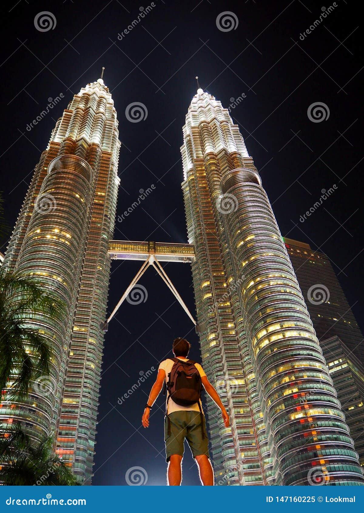 Verbaasde reiziger die omhoog aan de verlichte tweelingtorens van Petronas in Kuala Lumpur kijkt