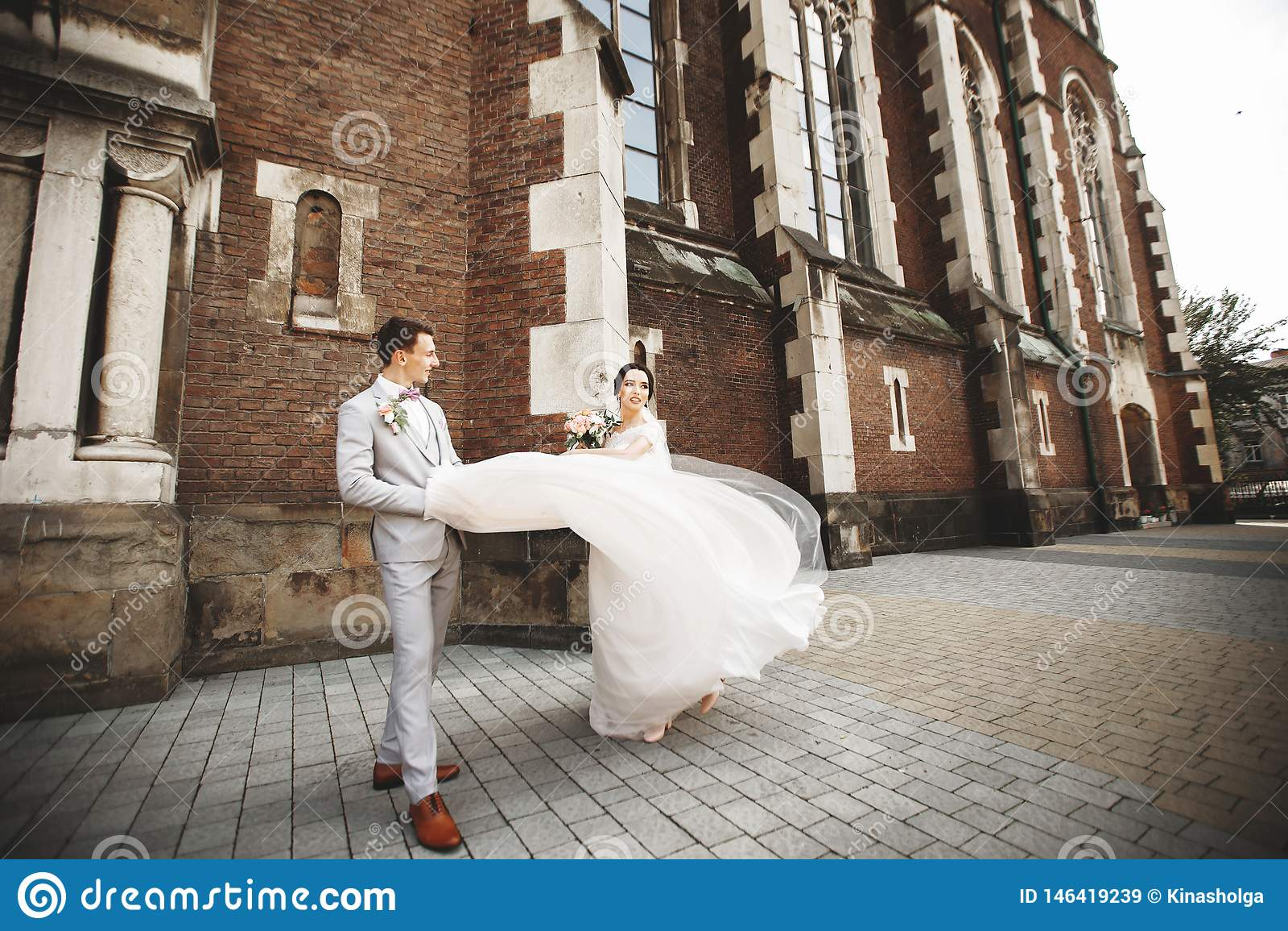 Verbazend glimlachend huwelijkspaar Mooie bruid en modieuze bruidegom dichtbij de kerk