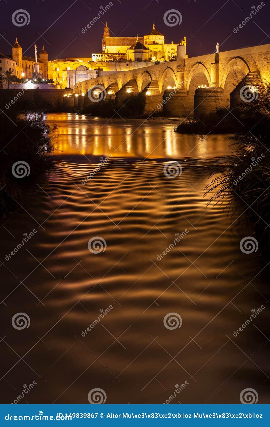 Verbazend panorama van Roman brug en Mezquita die van Cordoba in nacht gloeien