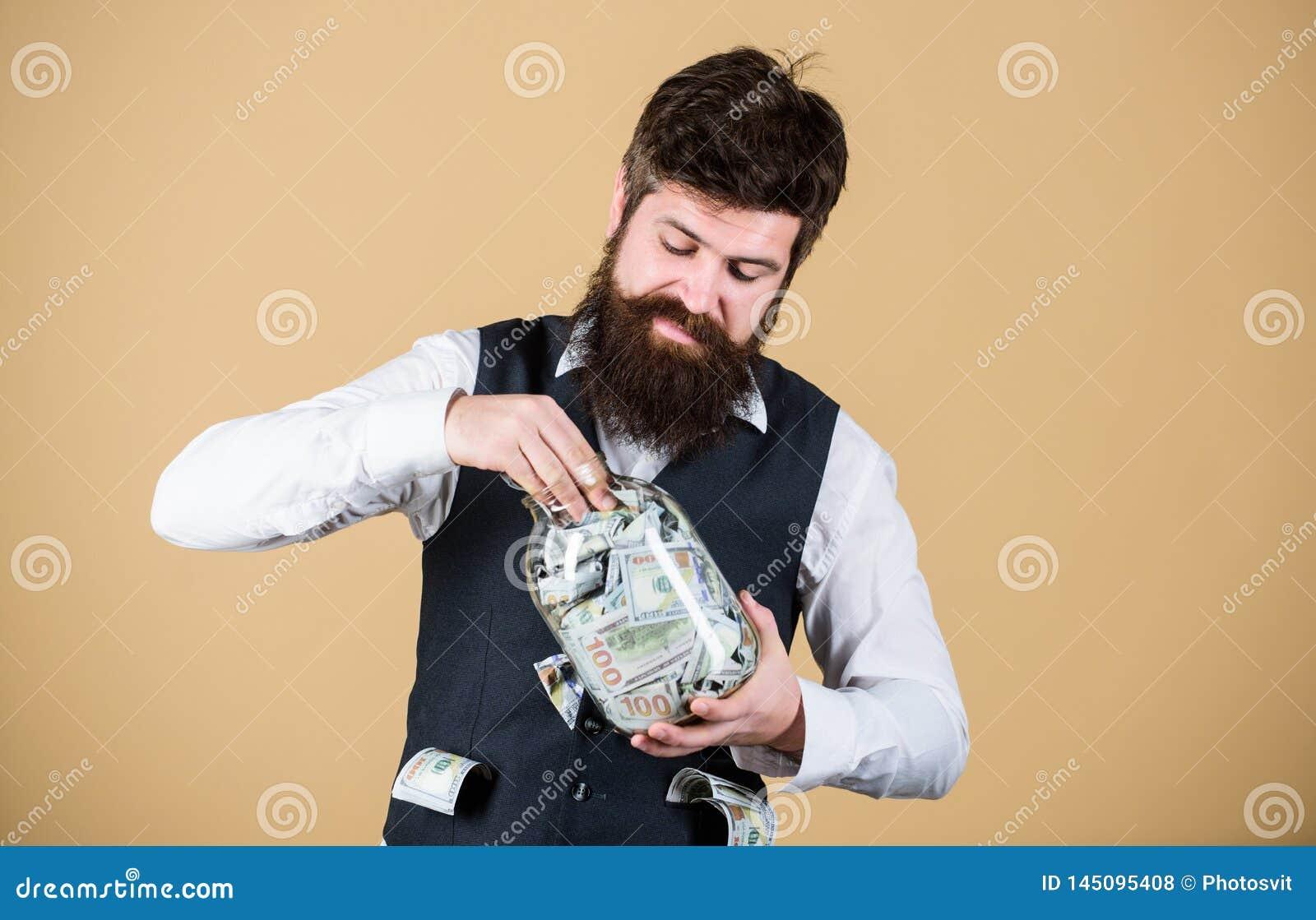 Verbergend geld voor toekomstig gebruik Gebaarde mens die geld van glaskruik investeren voor toekomstige winsten Zakenman die con
