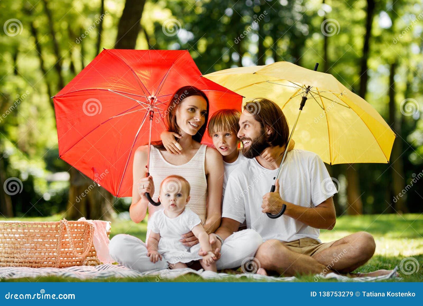 Verbergend van de zon onder grote rode en gele paraplu smoeder, zitten de vader en hun kinderen op de deken en