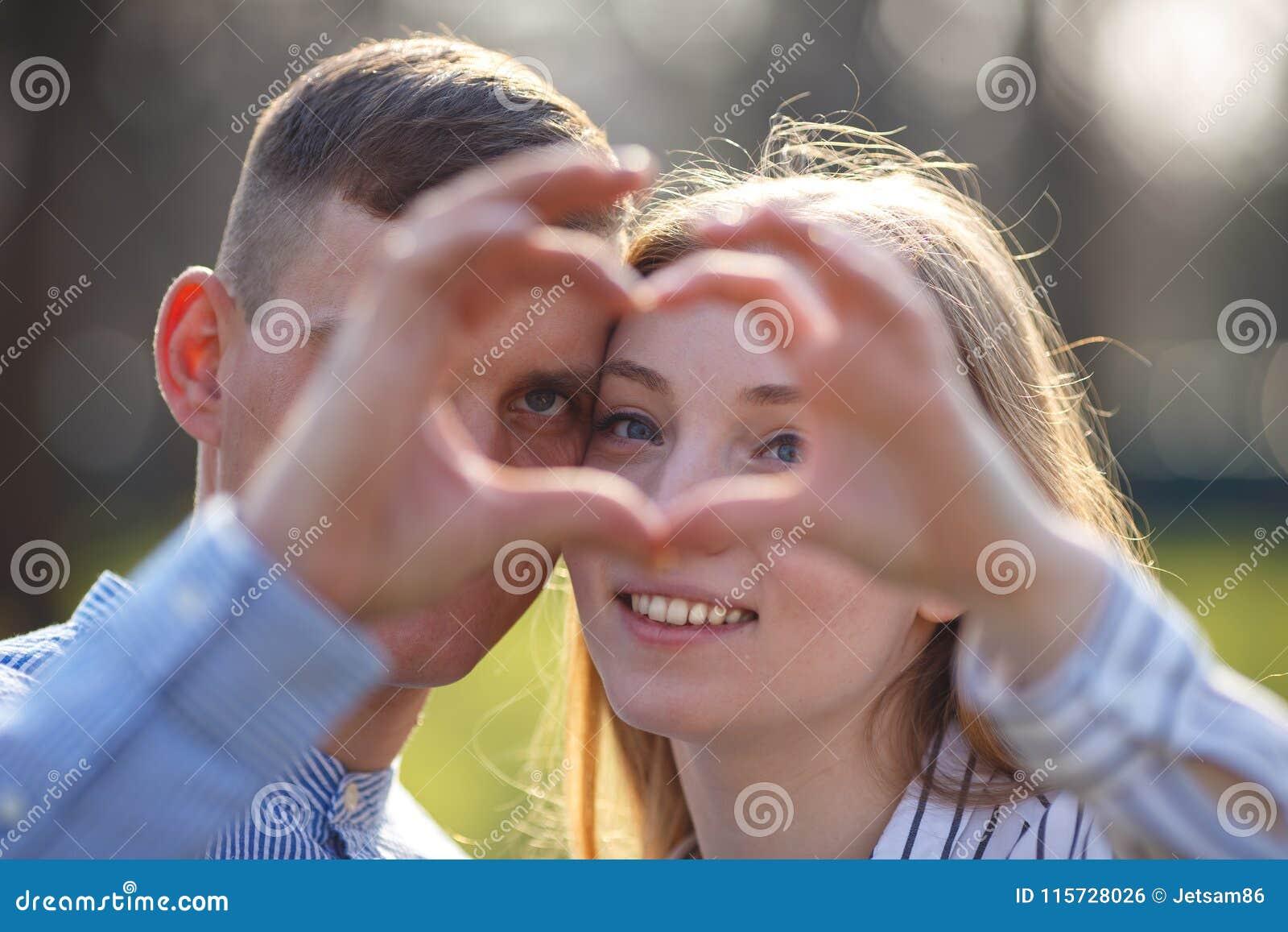 Verbinden Sie das Schauen durch ein Herz, das mit den Fingern gemacht wird