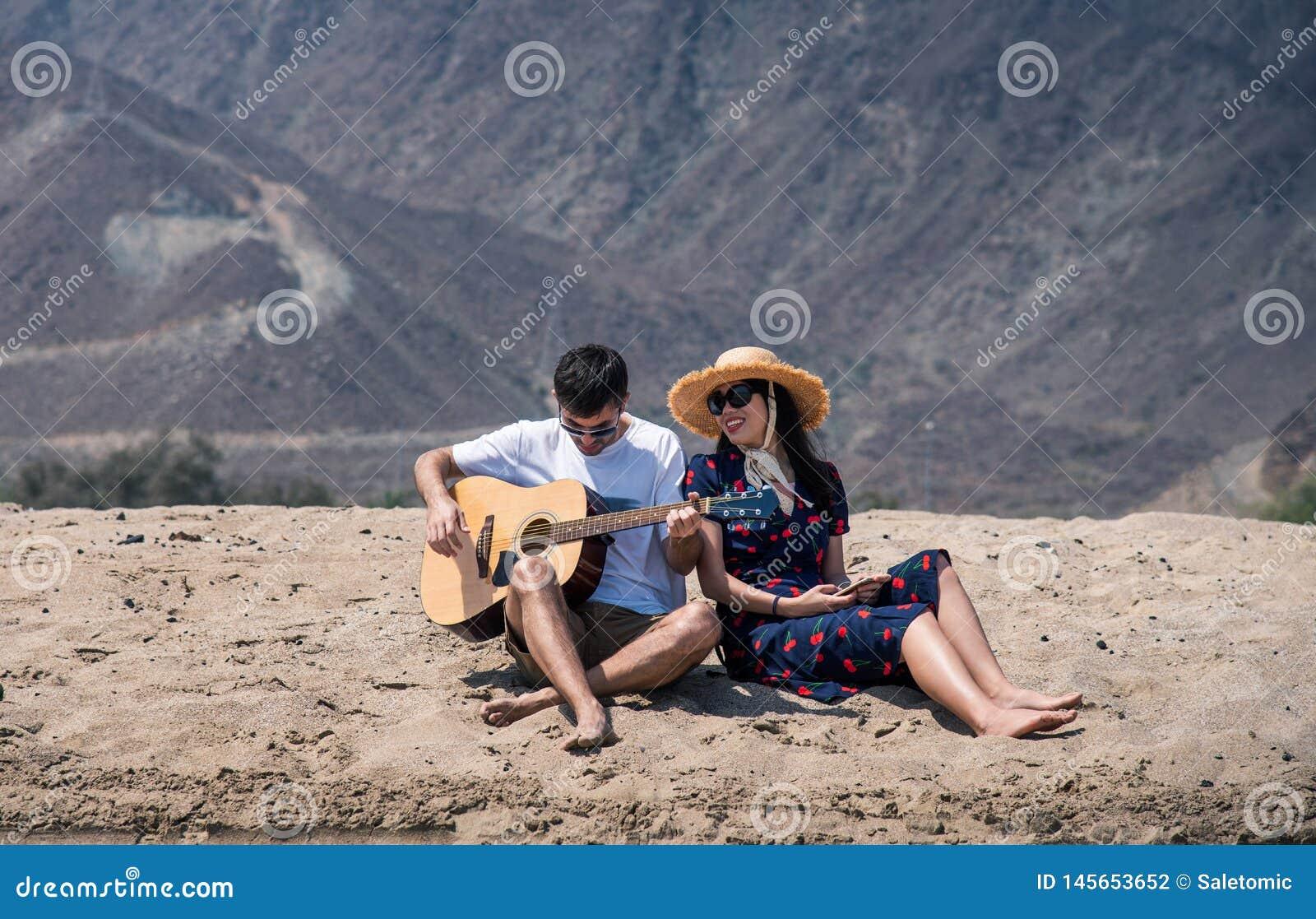 Verbinden Sie den Gesang und das Spielen der Gitarre, den Strand zu kaufen