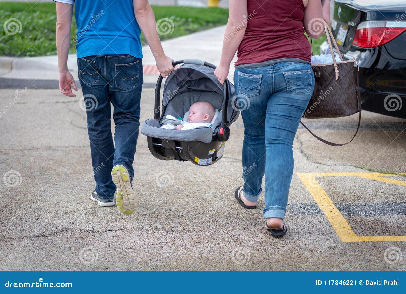 Verbinden Sie ein Baby in einem Autositz zusammen tragen
