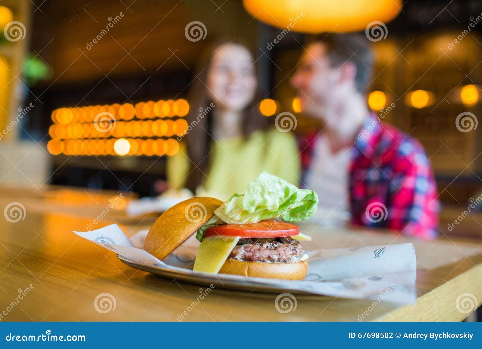 Verbinden Sie Mann und Frau - Essen des Hamburgers und Trinken in einem Schnellimbissrestaurant; konzentrieren Sie sich auf die M
