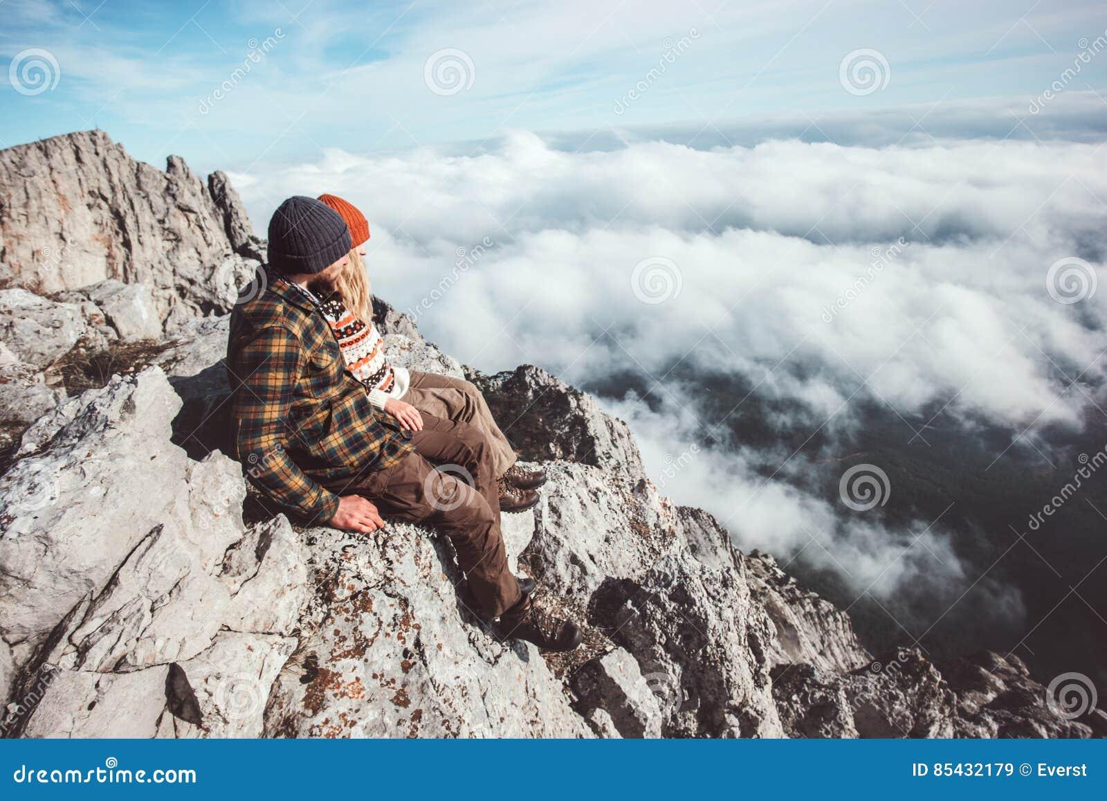 Verbinden Sie Reisende der Mann und Frau, die auf Bergen sitzen