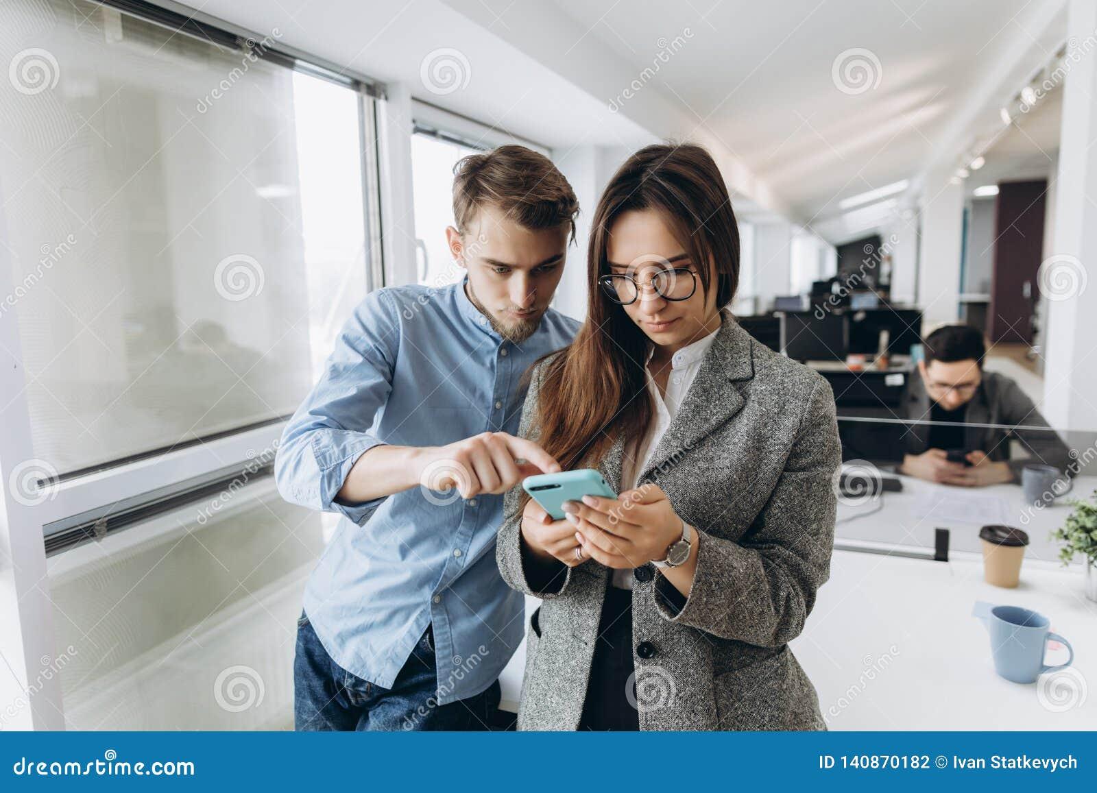 Verbinden Sie von den Mitarbeitern, die Studenten, die zusammen den Smartphone teilen und im kreativen Büro stehen