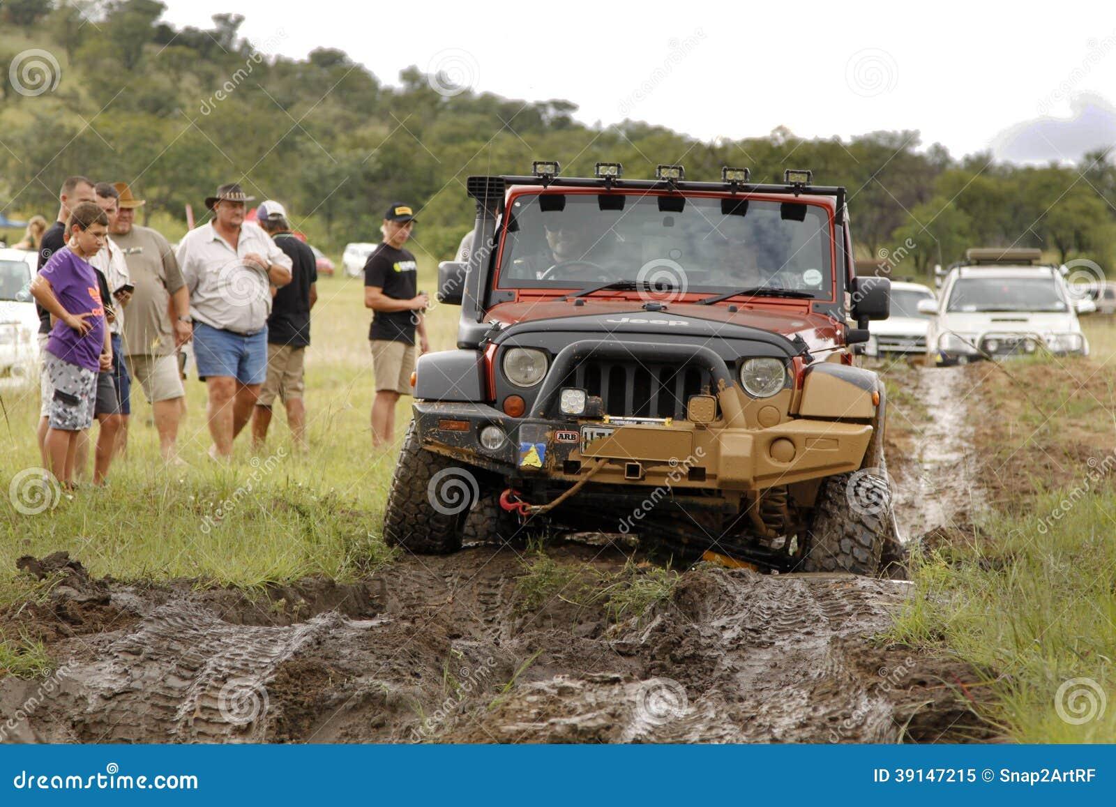 Verbrijzeling Beige Jeep Rubicon die modderhindernis kruisen
