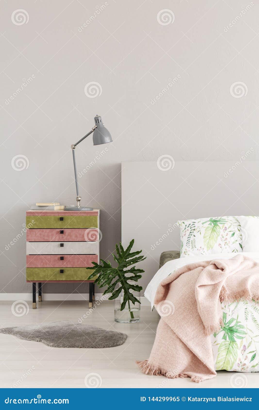 Verde azeitona e nightstand colorido cor-de-rosa pastel ao lado do vaso de vidro com a folha no interior simples do quarto, espaç