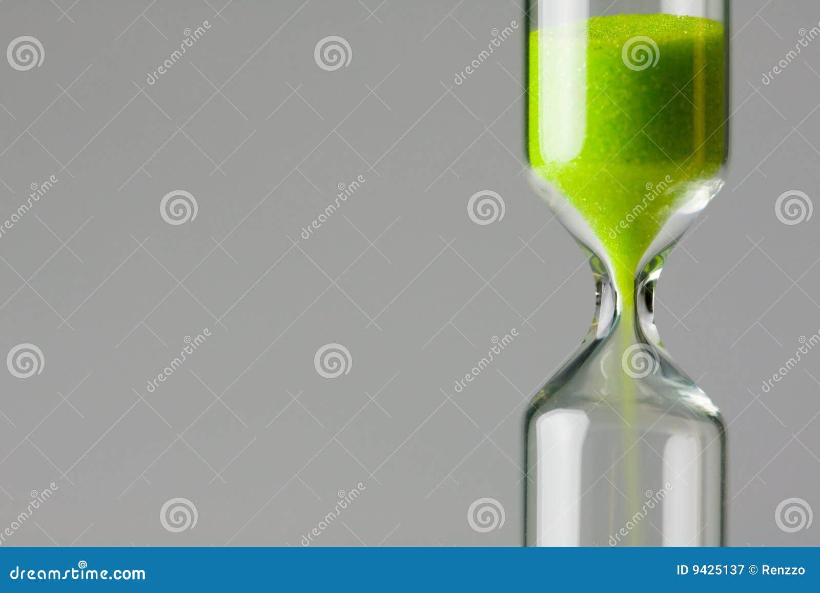 Verde de diminuição. Areia verde do vidro da hora