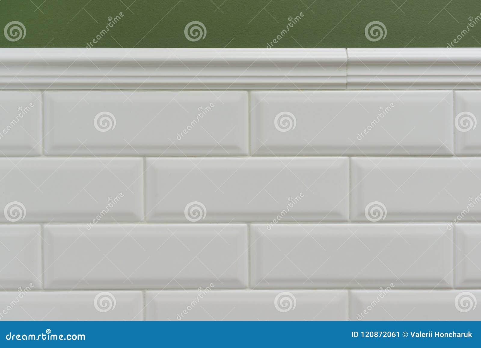 Verdissez le mur peint, une partie du mur est petite brique brillante blanche couverte de tuiles, tuiles décoratives en céramique