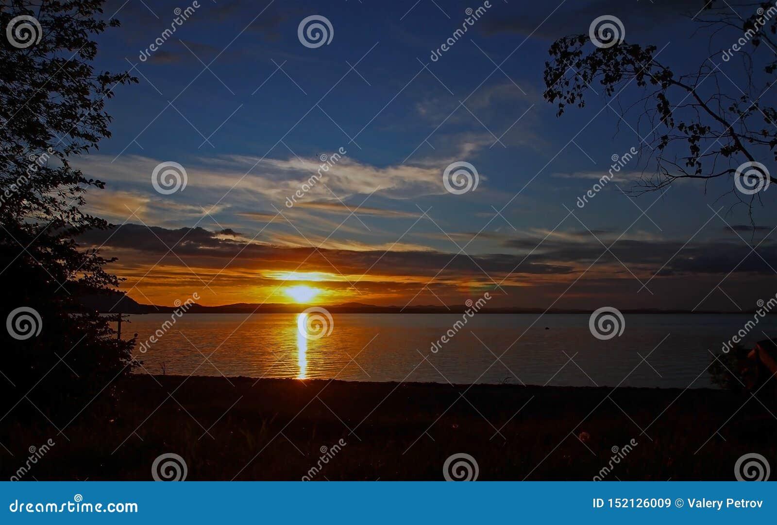 Verdonkerende zonsonderganghemel over het meer met kleurrijke wolken, Gouden uur