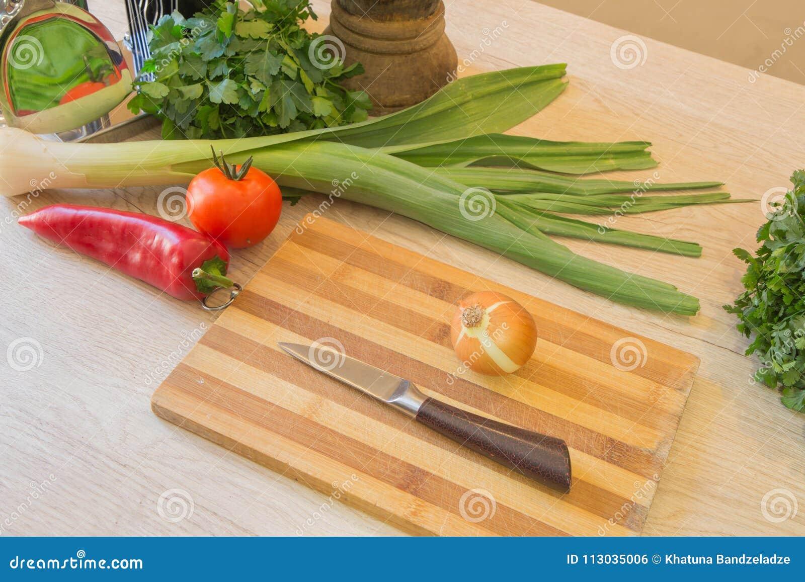 Verduras, cebolla y pimienta orgánicas frescas en piso de madera